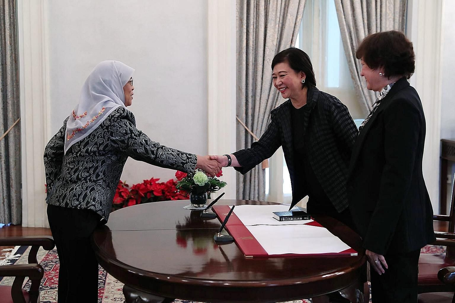 President Halimah Yacob shaking hands with Ms Chua Sock Koong, who took her oath before Judge of Appeal Judith Prakash at the Istana yesterday. Ms Chua is an alternate member of the Council of Presidential Advisers.
