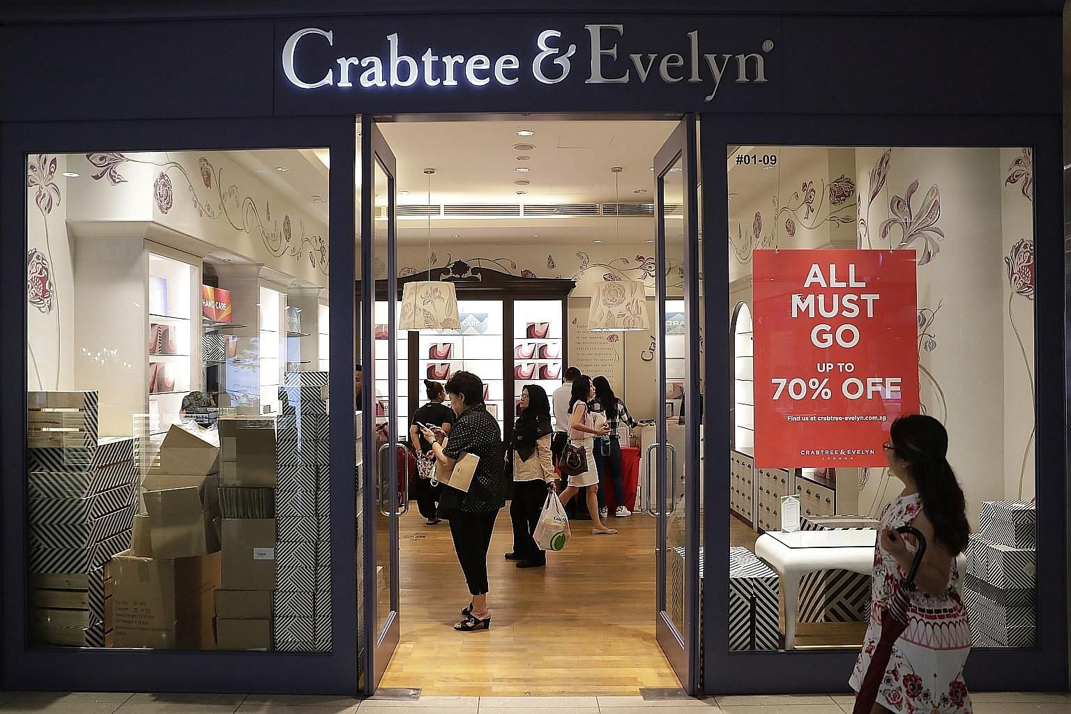 Half-empty shelves in Crabtree and Evelyn's VivoCity outlet yesterday. Long queues were seen at the United Kingdom-based bath and body product retailer's in-store closing-down sales in Singapore during the Christmas period, with discounts of up to 70