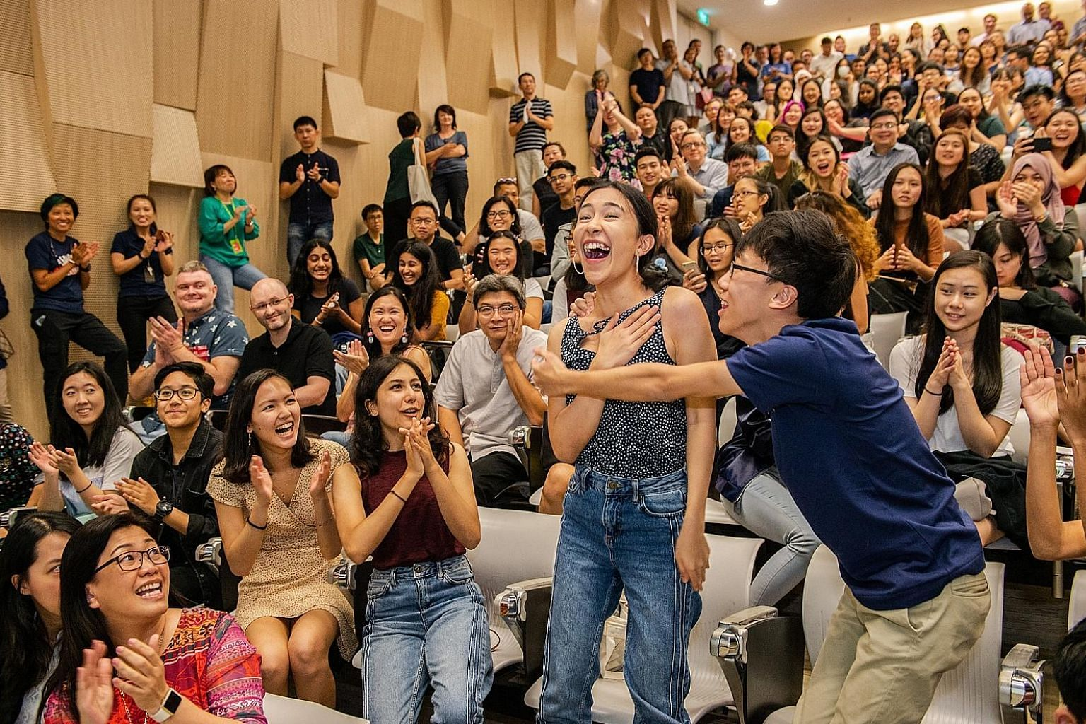 Students from the School of the Arts receiving their International Baccalaureate diploma exam results at the school yesterday. Almost all of the 2,152 students here - or 97.99 per cent - who sat the exams last November passed.
