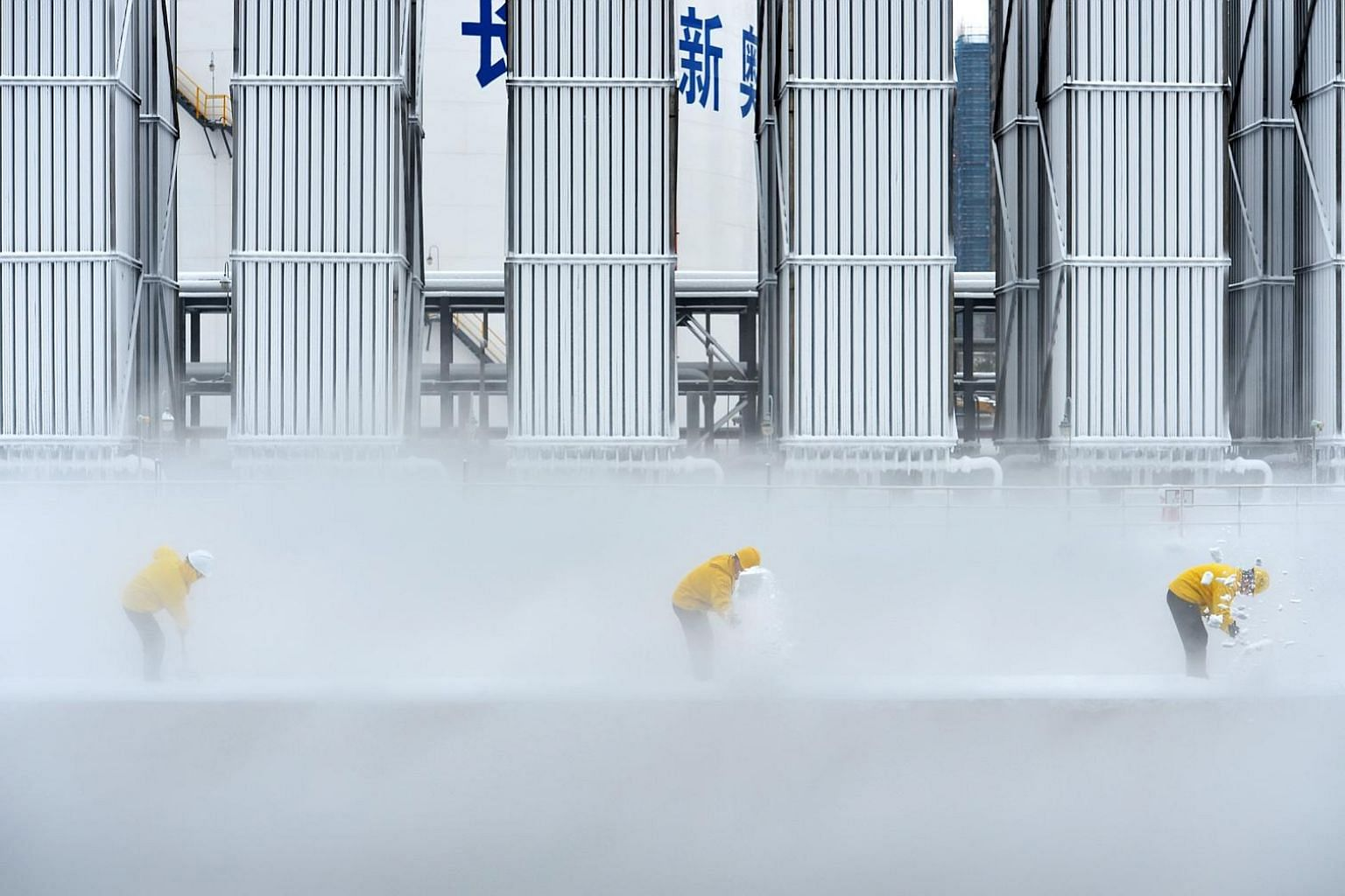 Workers removing snow at a liquefied natural gas facility of ENN Group in Changsha, in China's Hunan province, earlier this week. A final investment decision could be taken on more than 60 million tonnes per annum of LNG capacity this year, well abov