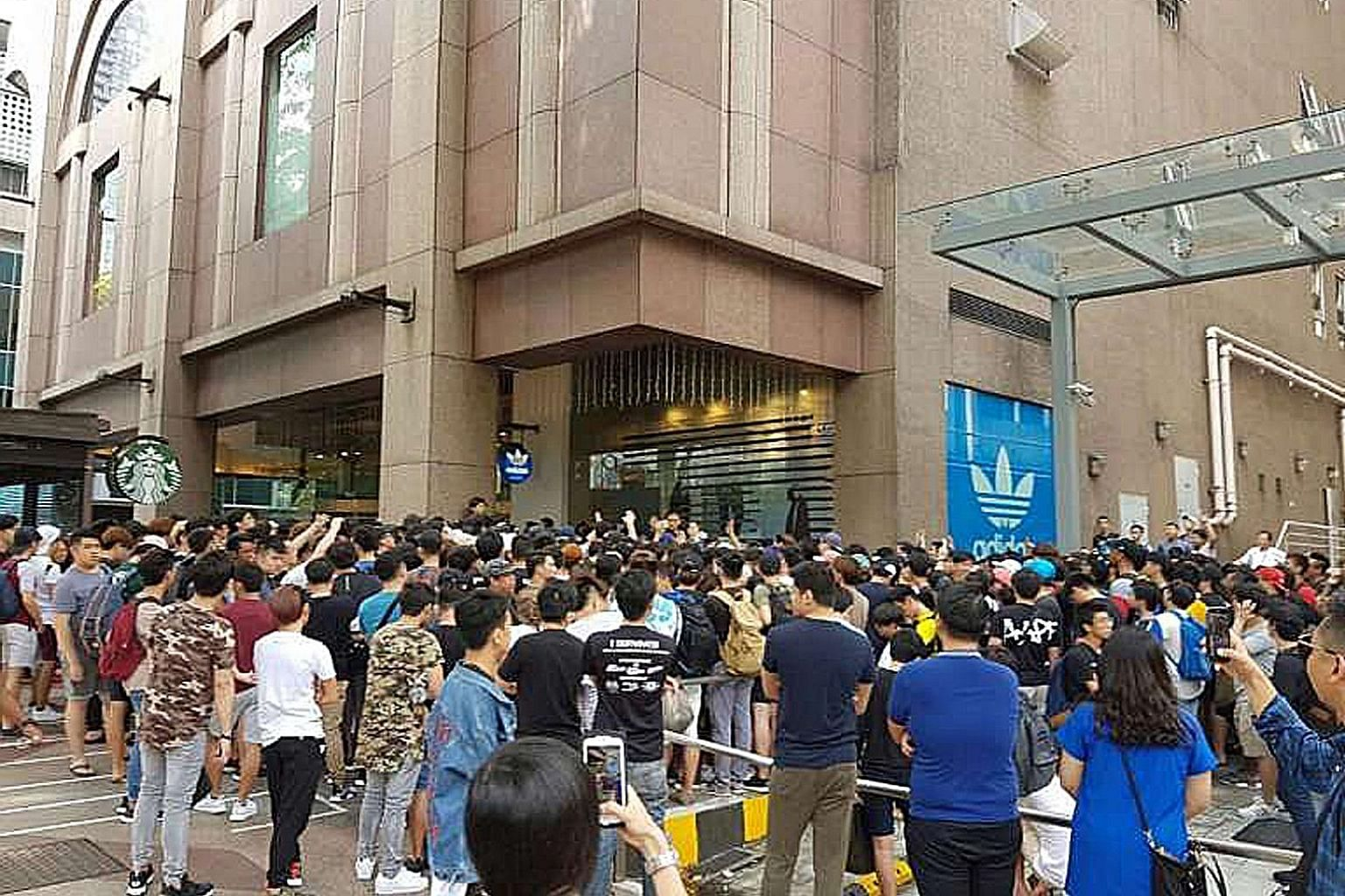 "A crowd outside the adidas Originals store at Pacific Plaza. The evolution of business models to focus on athleisure - a combination of ""athletics"" and ""leisure"" - has fuelled a sector dominated by giants like Nike and adidas."