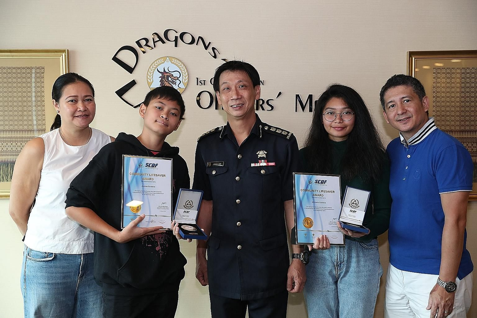 Colonel Lim Boon Hwee, Commander of the 1st SCDF Division, with (from left) Mrs Laureen Cordova, her son Joshua, daughter Mikkaela, and husband Jun. With the help of her brother, Miss Cordova pulled out an unconscious boy from the 2.4m-deep pool at M