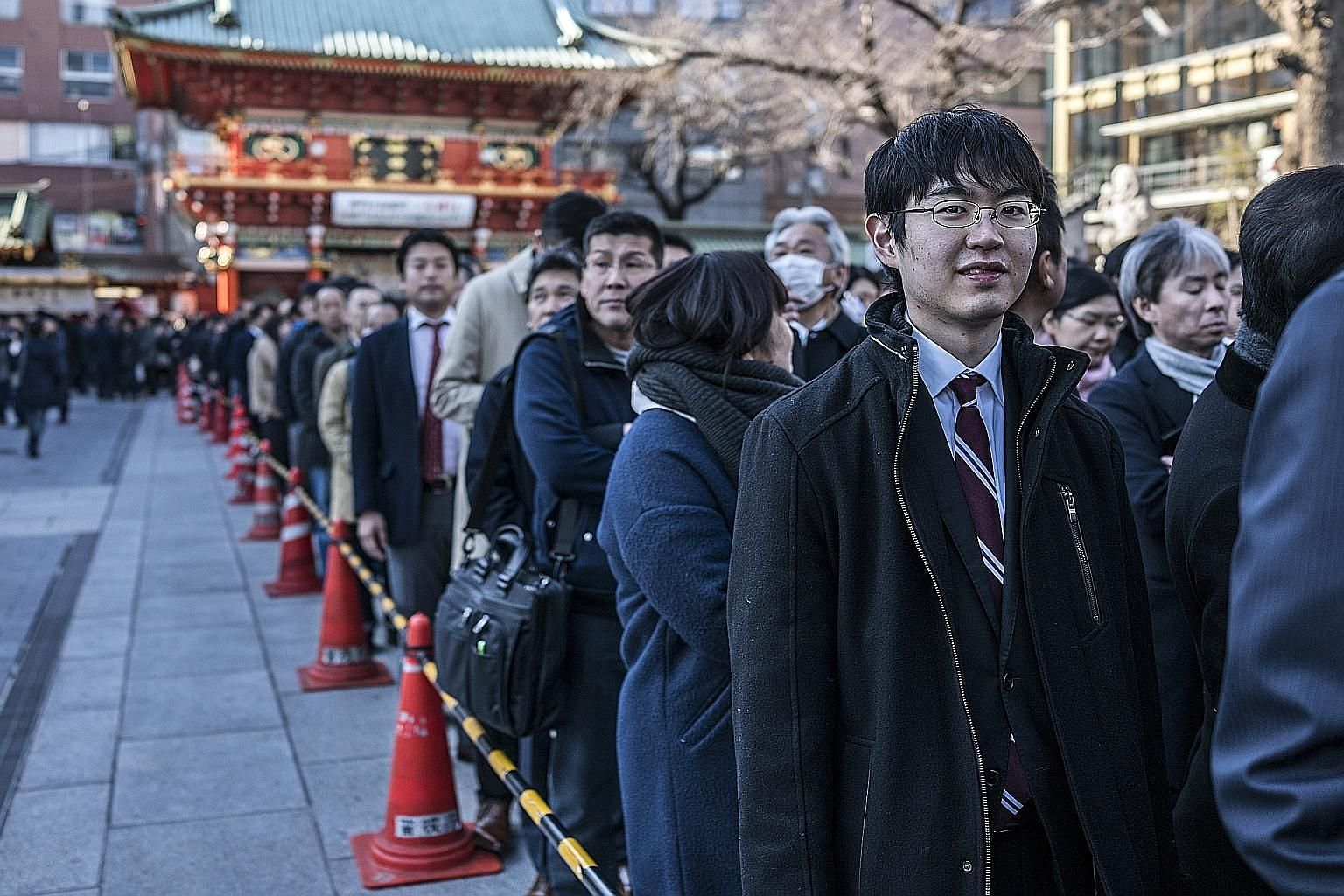Japanese lining up yesterday to offer prayers on the first business day of the year at Kanda Myojin, a Shinto shrine in Tokyo. The Japanese currency not only surged almost 4 per cent against the US dollar on Thursday, but it also clocked its best mon
