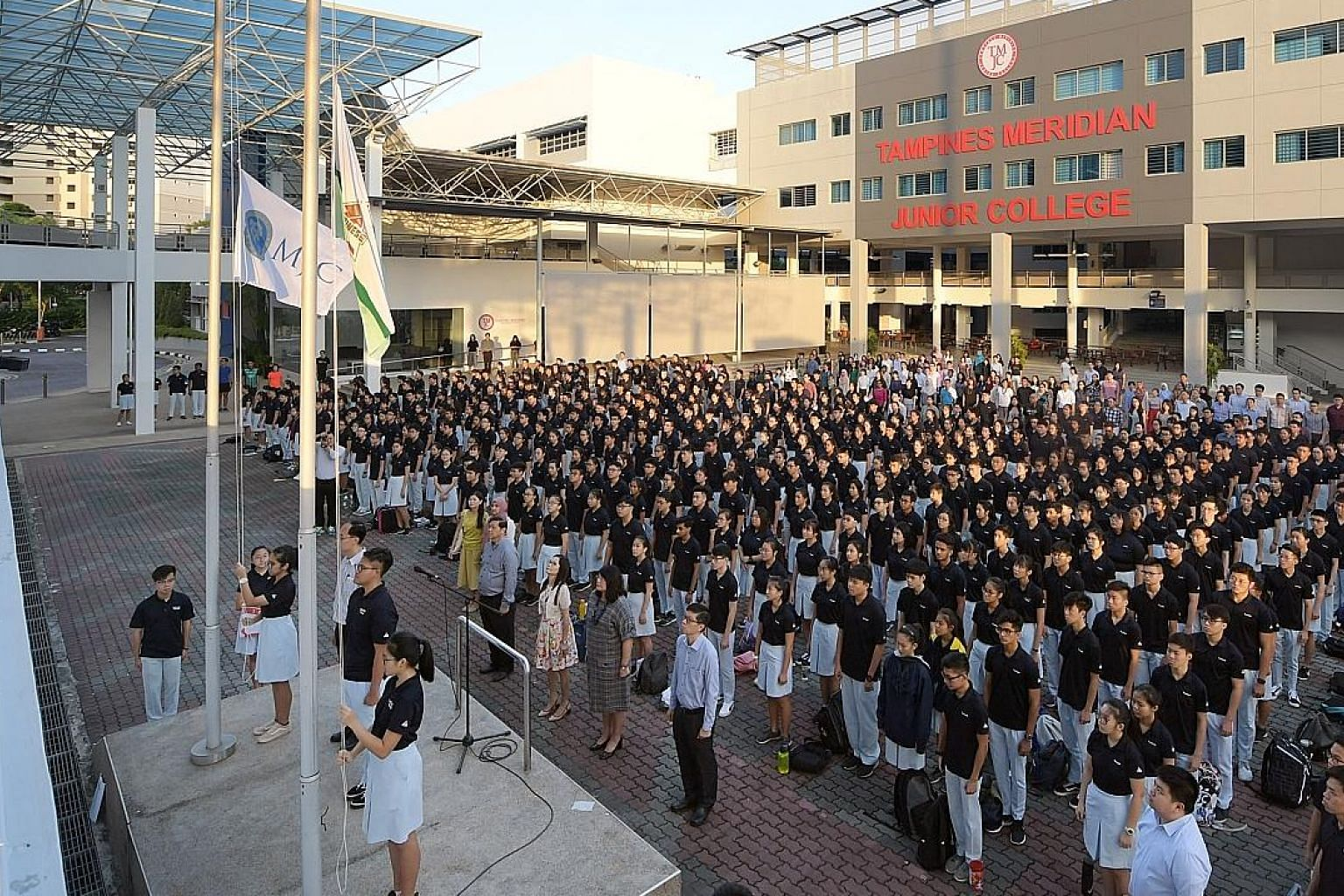The TMJC flag and state flag being raised. Students will get to shape the college's new culture, with the school song yet to be written. Tampines Meridian Junior College students watching as the old flags of Tampines JC and Meridian JC were lowered o