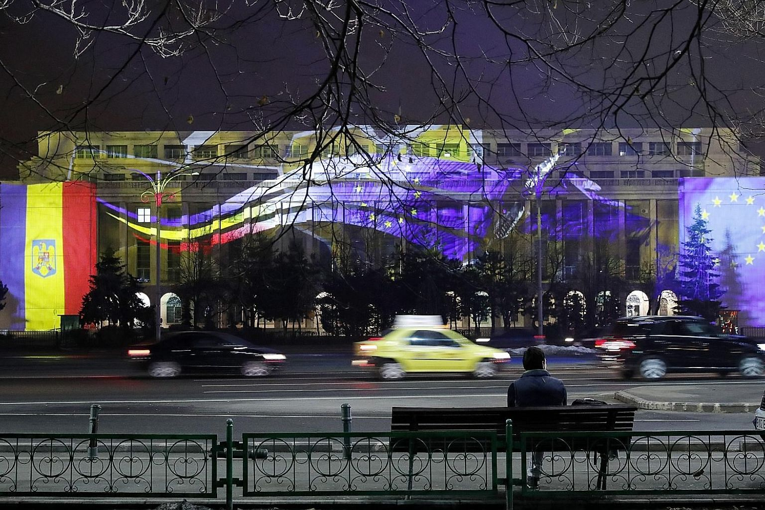 Victoria Palace - the Romanian government headquarters - with the flags of Romania (left) and European Union projected on its facade to mark the country's EU presidency for half a year from this month.