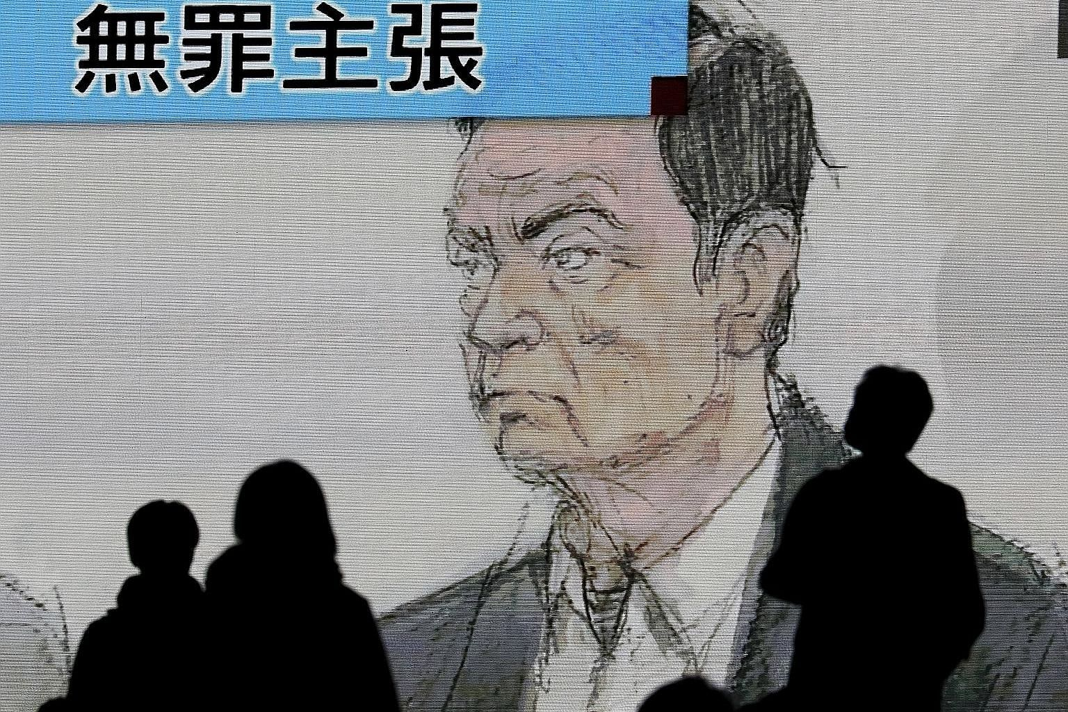 Pedestrians watching a news clip featuring ousted Nissan chairman Carlos Ghosn during his court appearance in Tokyo yesterday.