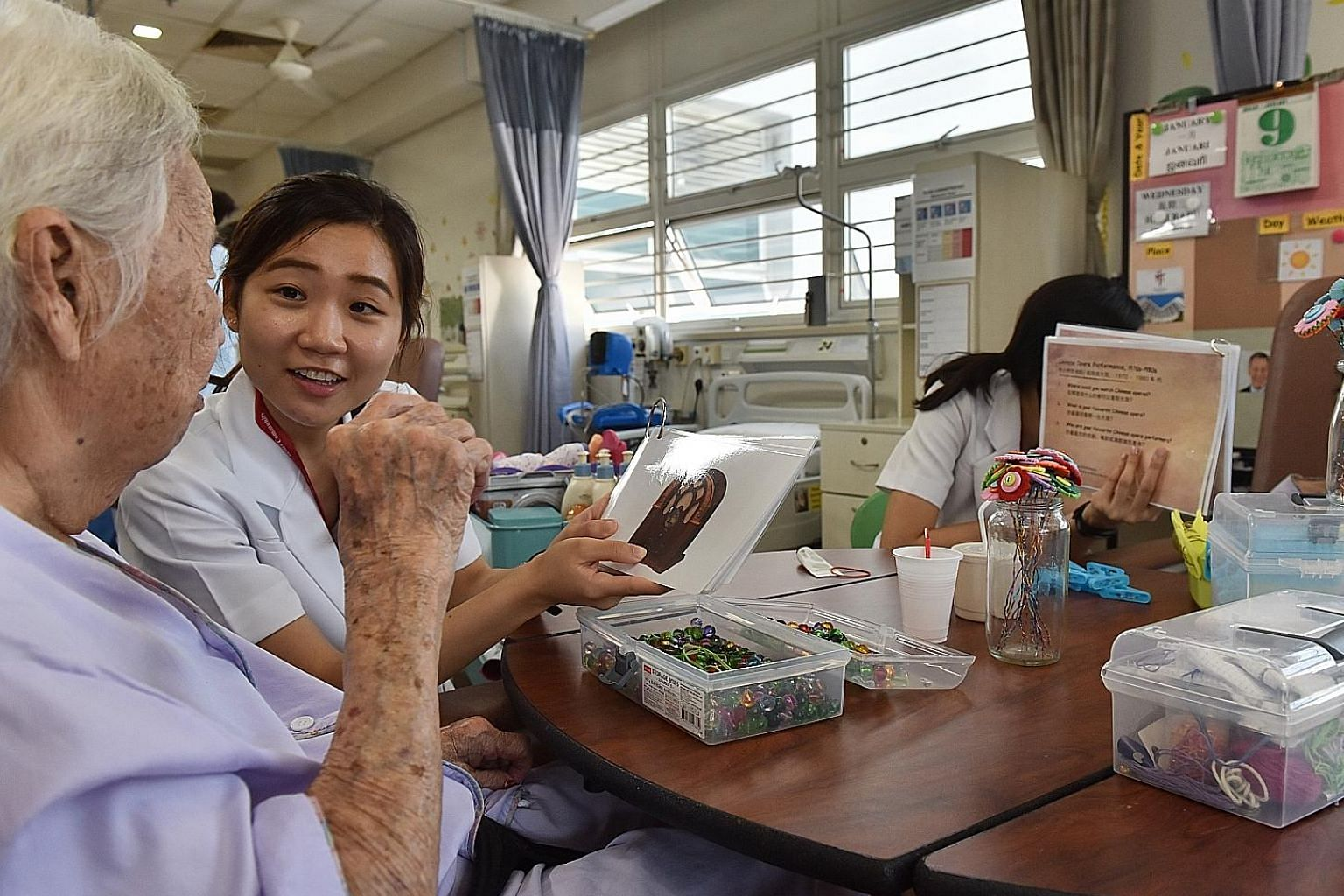Research assistant Eileen Fabia Goh engaging a patient with flash cards in Tan Tock Seng Hospital's Subacute Geriatric Monitoring Unit. The ward caters to female patients admitted for other medical conditions but also suffer from dementia-related del