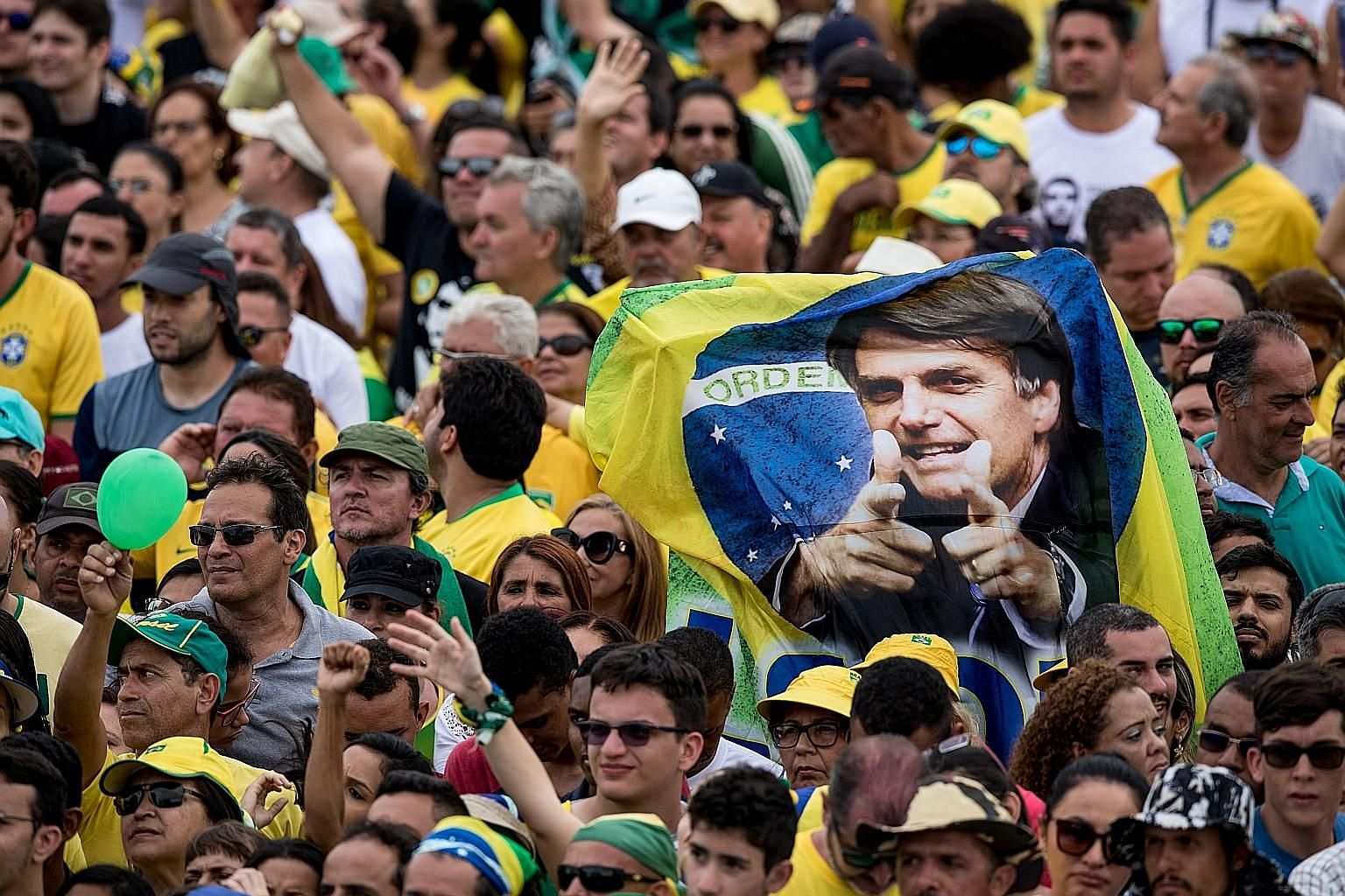 Supporters of Brazil's newly-elected President Jair Bolsonaro with a banner bearing his photo. The writer argues that the right-wing Mr Bolsonaro and others with similar leanings have ridden to power by capitalising on the growing animus against the