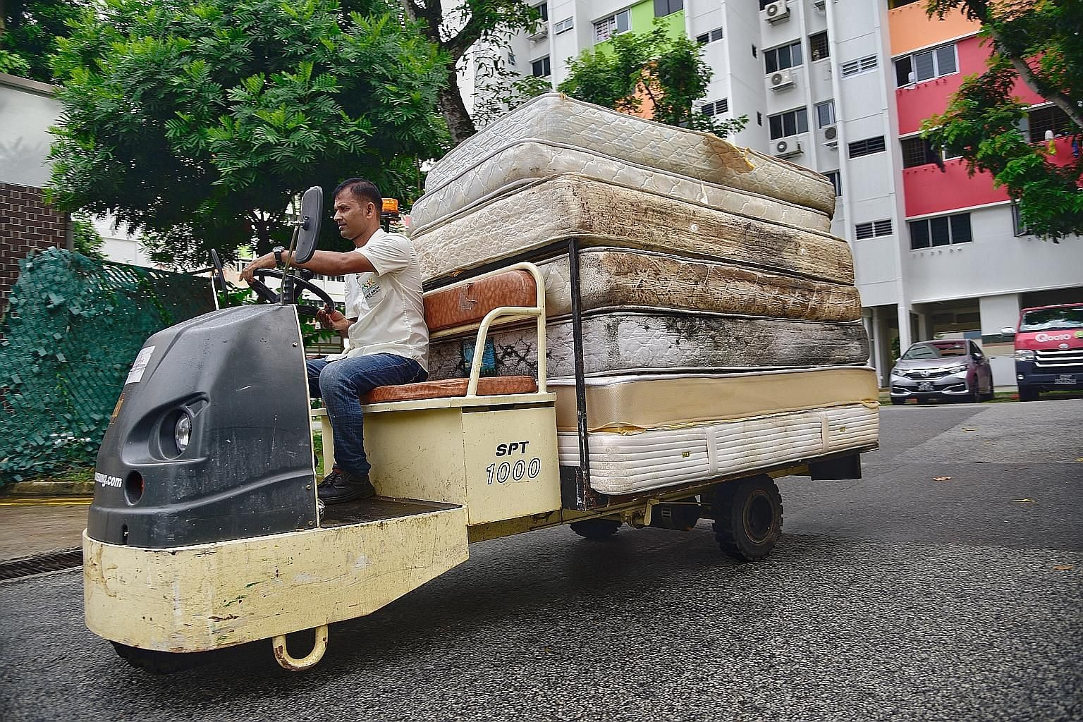 Junior college student Chow Xin Tian has been using the Renew bins at StarHub for her used computer parts and electronic products. A worker from Nee Soon Town Council drives a battery-operated cart with discarded mattresses to a bin centre in Yishun
