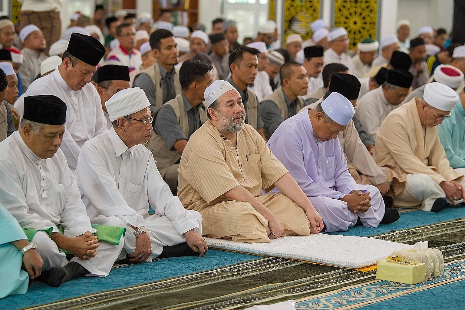 TOP: Sultan Muhammad V attending prayers at Masjid Al Sultan Ismail Petra in Kelantan. He is often seen in a jubah and mingles easily with the people. ABOVE: The Sultan Muhammad II Mosque is a few metres away from Istana Telipot and is frequented by