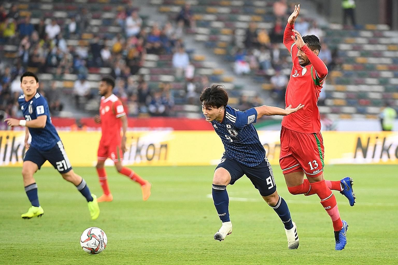 Japan's forward Takumi Minamino evading the attentions of Oman's Khalid Al-Braiki during their Group F game at the Hazza bin Zayed Stadium in Abu Dhabi. Japan won 1-0.