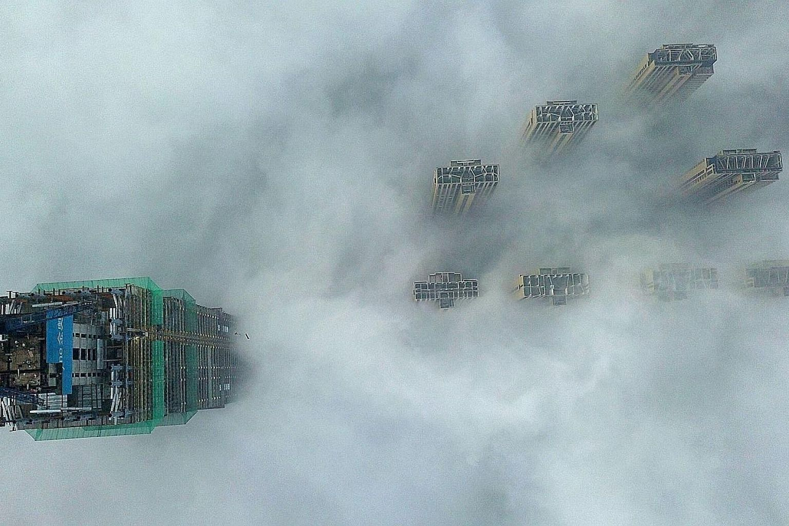 This aerial view shows the tops of high-rise buildings poking out from heavy fog in Yangzhou, in China's eastern Jiangsu province. The authorities in the city issued a red alert - the highest level - for heavy fog yesterday, with visibility reduced t