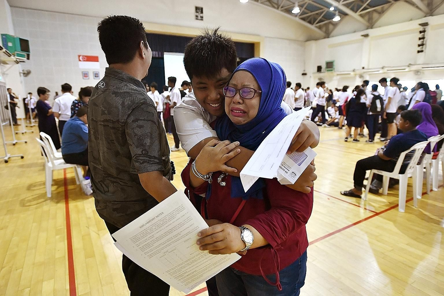 Norman Adli Ramli, 16, hugging his mother, Madam Norlizah Abdul Kahar, 40, a bank officer, after he received his O-level results at Serangoon Garden Secondary School yesterday. He did well enough to qualify for junior college. Students who sat last y