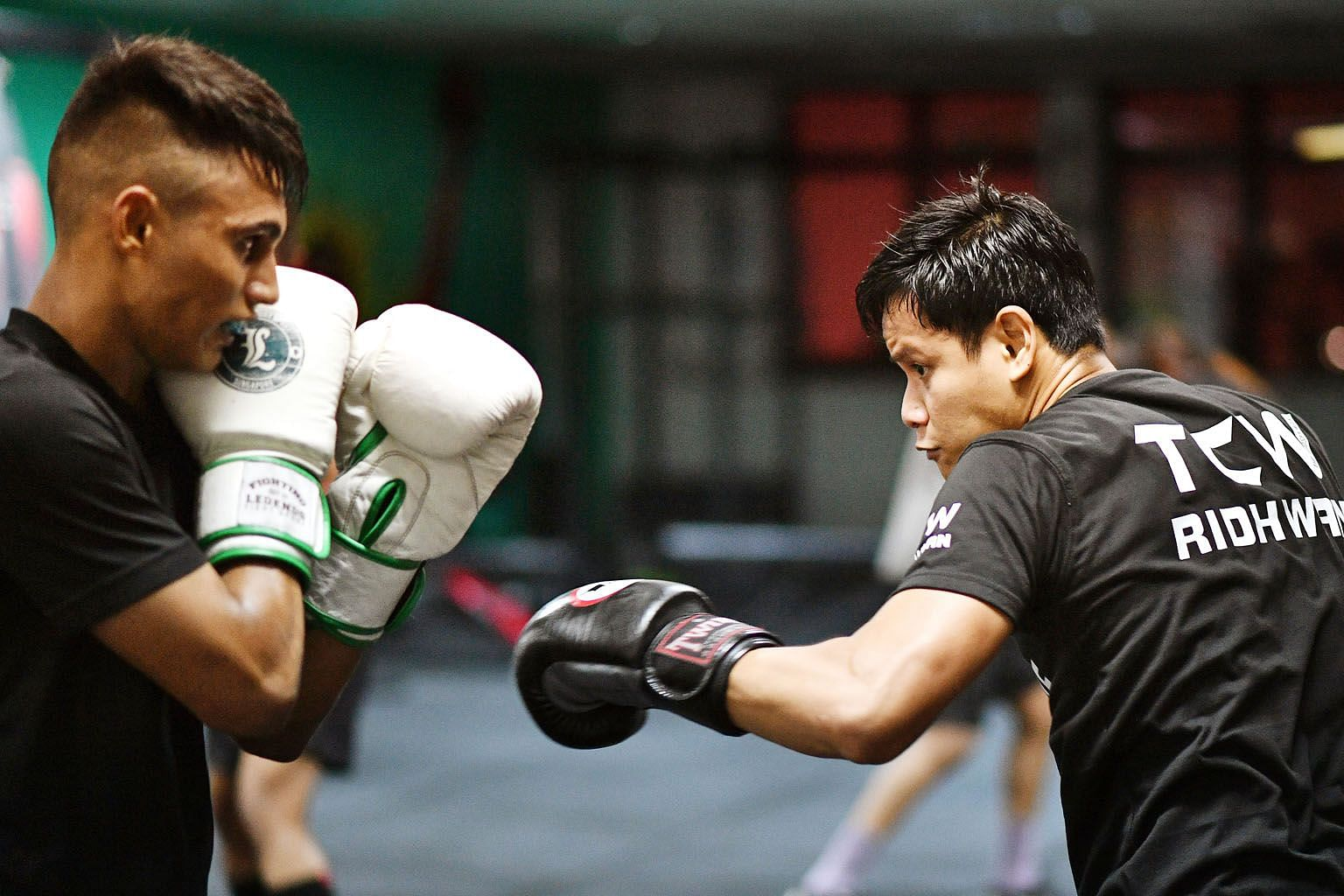 Ridhwan (right) sparring with an at-risk youth under The Chosen Wan (TCW) Cares Programme. His March 29 bout is a rematch of his split-decision loss to Namibian Paulus Ambunda last September.