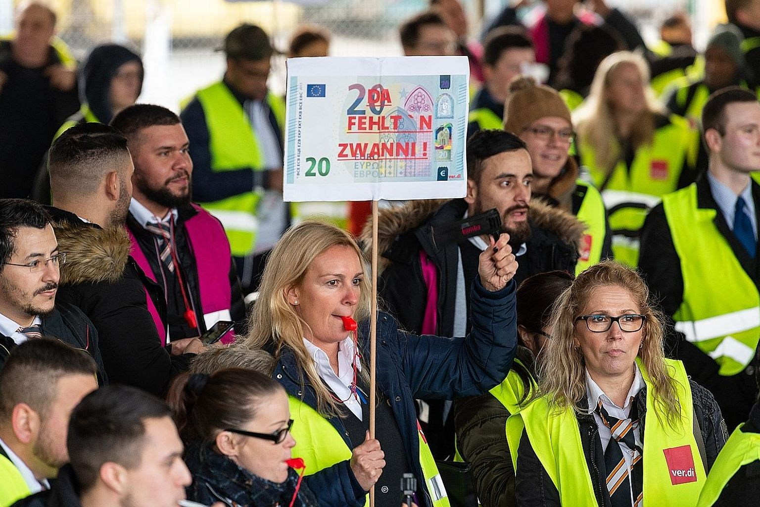 A security worker holding a sign depicting €20 during a strike at Frankfurt Airport yesterday.