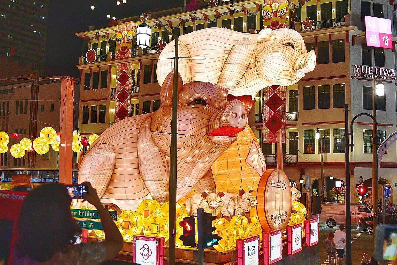 The centrepiece of this year's Chinese New Year display in Chinatown features pigs perched on top of a lantern depicting a bulging purse overflowing with gold coins.