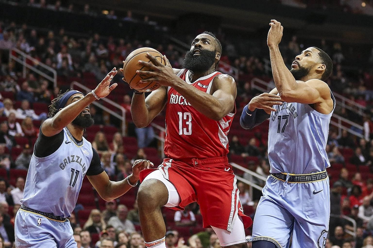 Houston Rockets guard James Harden making light of the defensive efforts of Memphis Grizzlies' Mike Conley (No. 11) and guard Garrett Temple as he drives to the basket during the Rockets' 112-94 win. Harden scored 57 points, the third game in which h