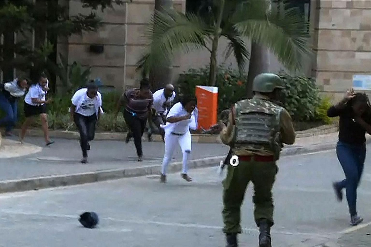 Above: TV footage shows people fleeing the scene amid a gunfight following a blast at the hotel and office complex in Nairobi. Left: People being evacuated from the hotel compound where explosions and gunshots were heard.