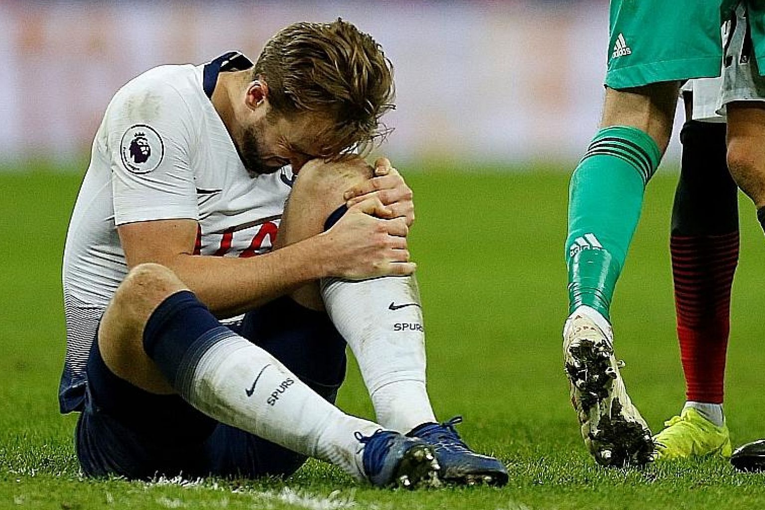 Tottenham striker Harry Kane holding his leg in pain during the 1-0 Premier League defeat by Manchester United on Sunday. The club have confirmed that he is out with ankle ligament damage.