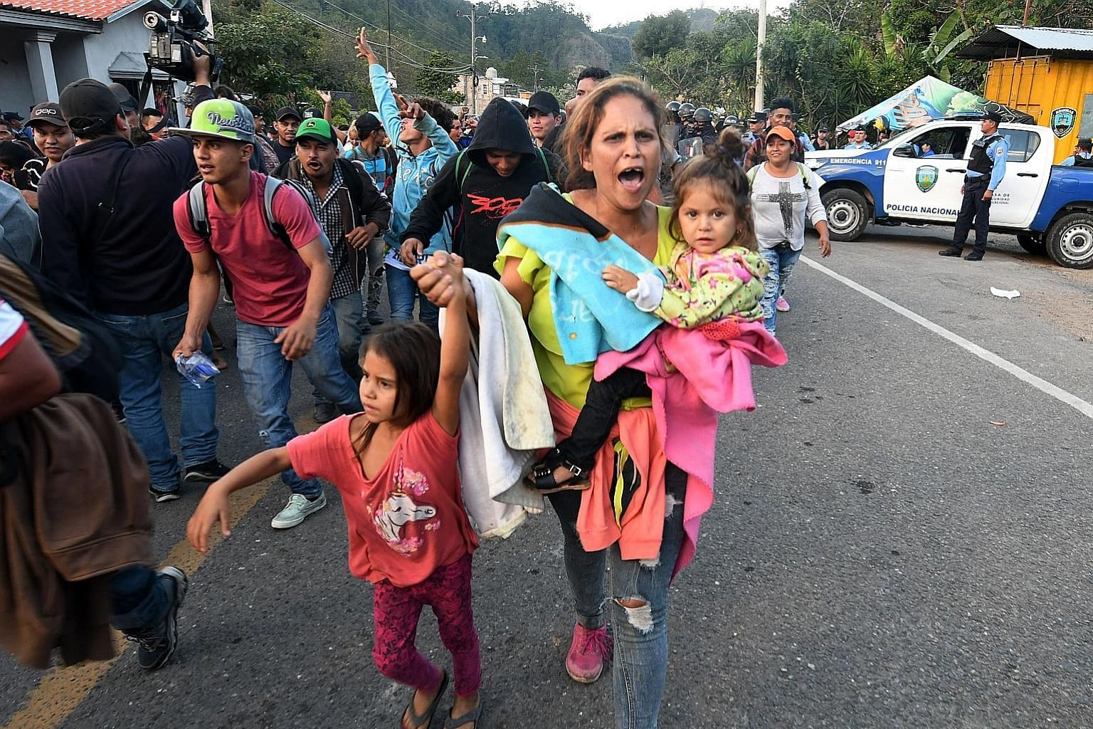 Honduran migrants marching on after breaking through a police cordon in Agua Caliente. Nearly 150 were turned away because they lacked documents.