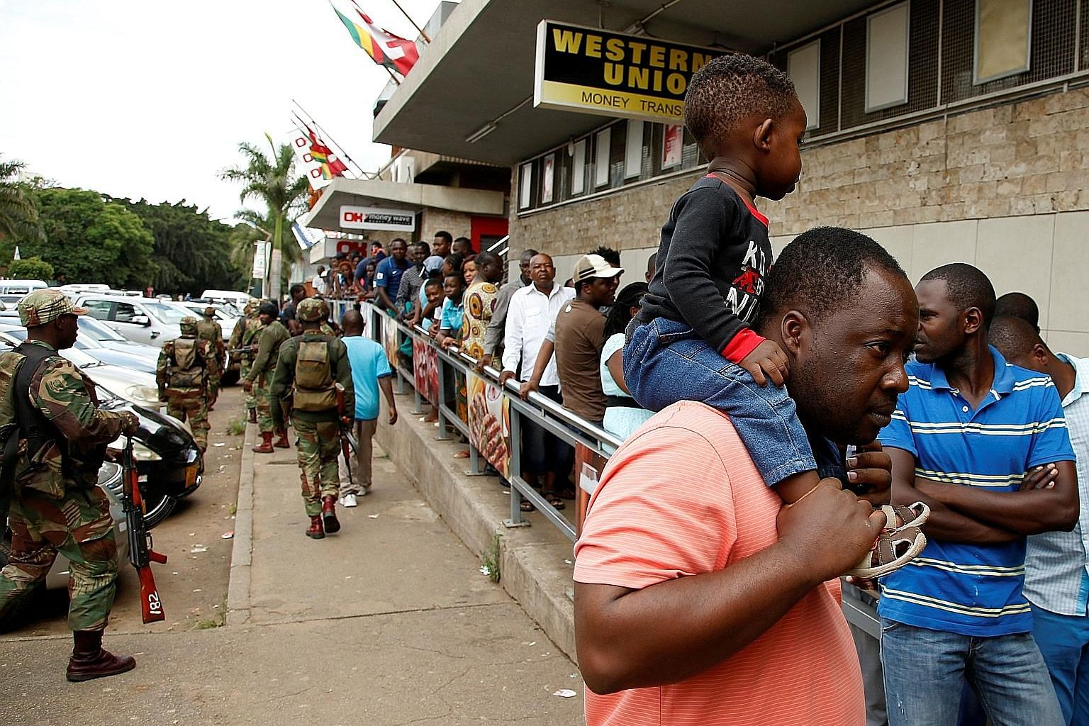 Armed soldiers patrolling the streets as people queue at a supermarket in Harare, Zimbabwe, yesterday. The capital was gripped by three days of protests after President Emmerson Mnangagwa increased the price of fuel by more than 150 per cent. Many ac