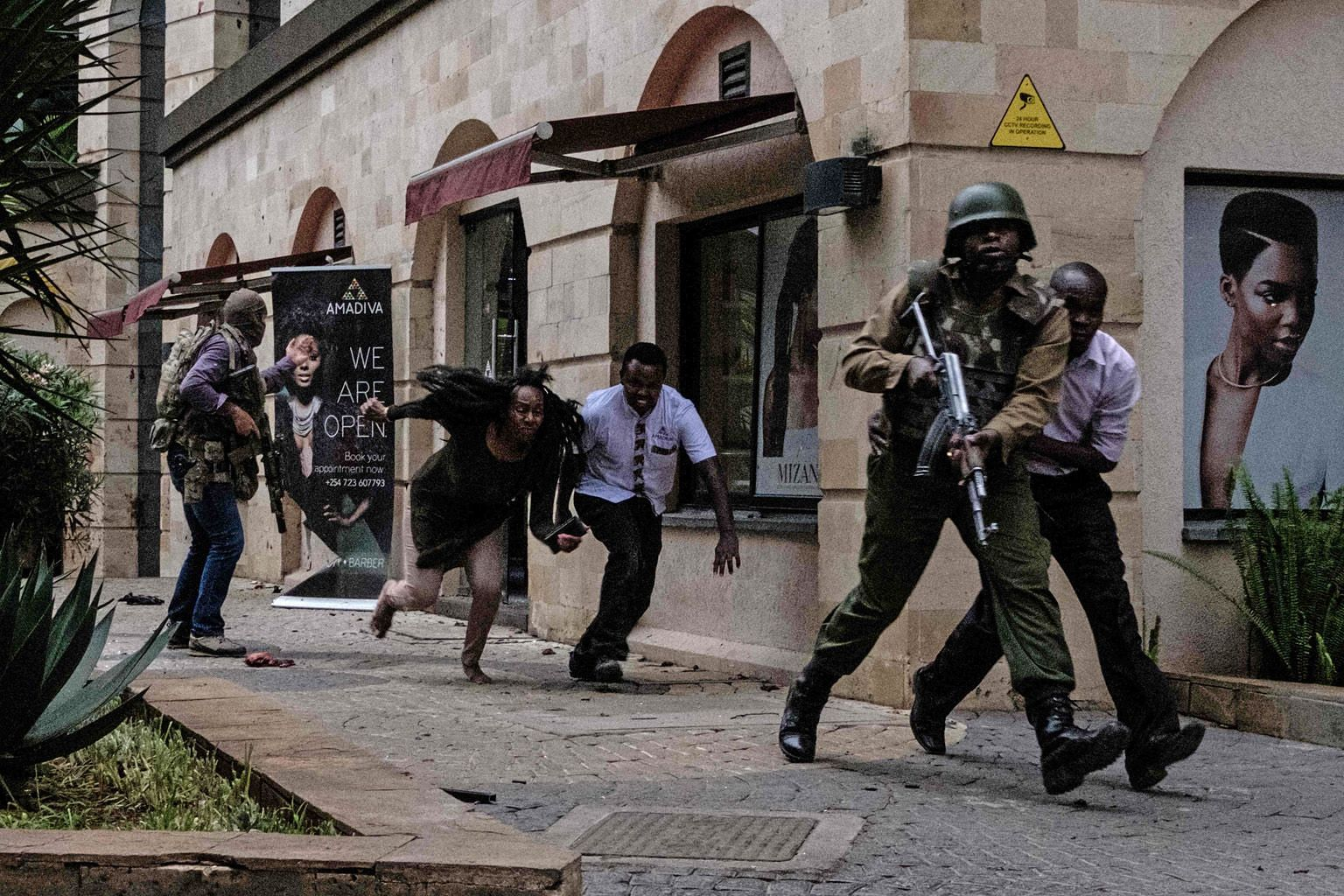 Kenyan security personnel helping people to escape after militants stormed into the hotel on Tuesday.