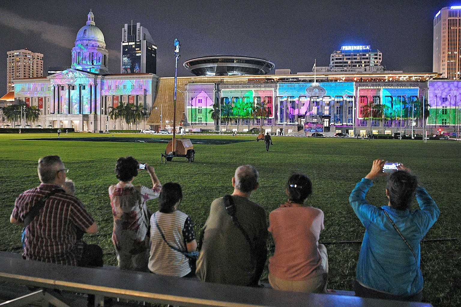 Viewers (above) enjoying a light show projected on the facade of the National Gallery Singapore at a media preview last night of the Light to Night Festival, which returns for a bumper edition until Feb 24. The Odyssey, commissioned by Art Skins on M