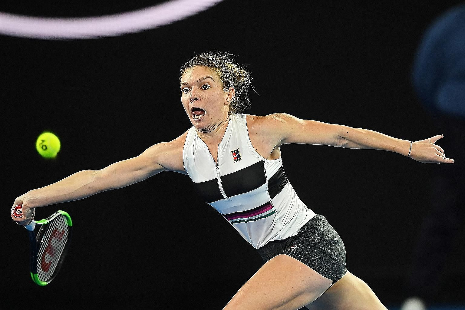 Simona Halep stretching to hit a forehand against Sofia Kenin of the USA during their second-round match. The Romanian came through three sets and pain in her thigh to progress.