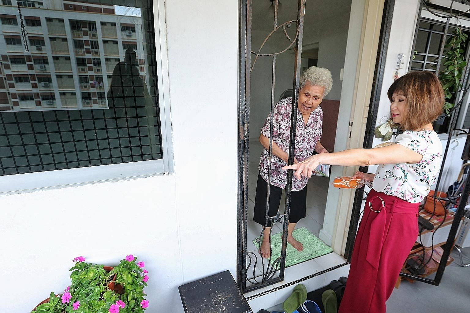 Dr Amy Khor visiting residents at Jurong West Street 73 to share dengue prevention tips yesterday.