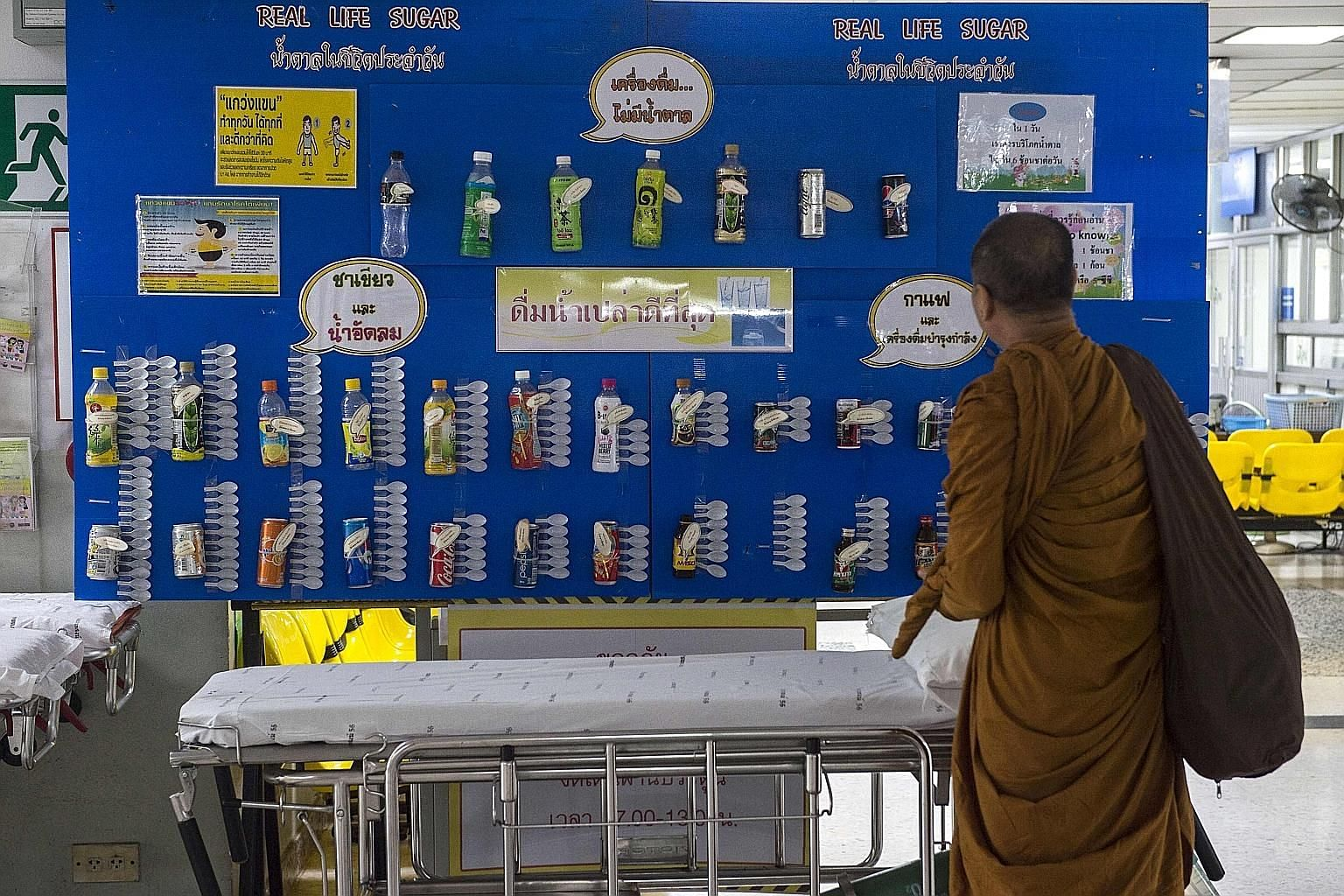 A monk checking out a display showing the sugar content of various drinks at a hospital in Bangkok. Latest available data on the website of the Office of the Cane and Sugar Board shows Thais' sugar consumption from January to September last year was