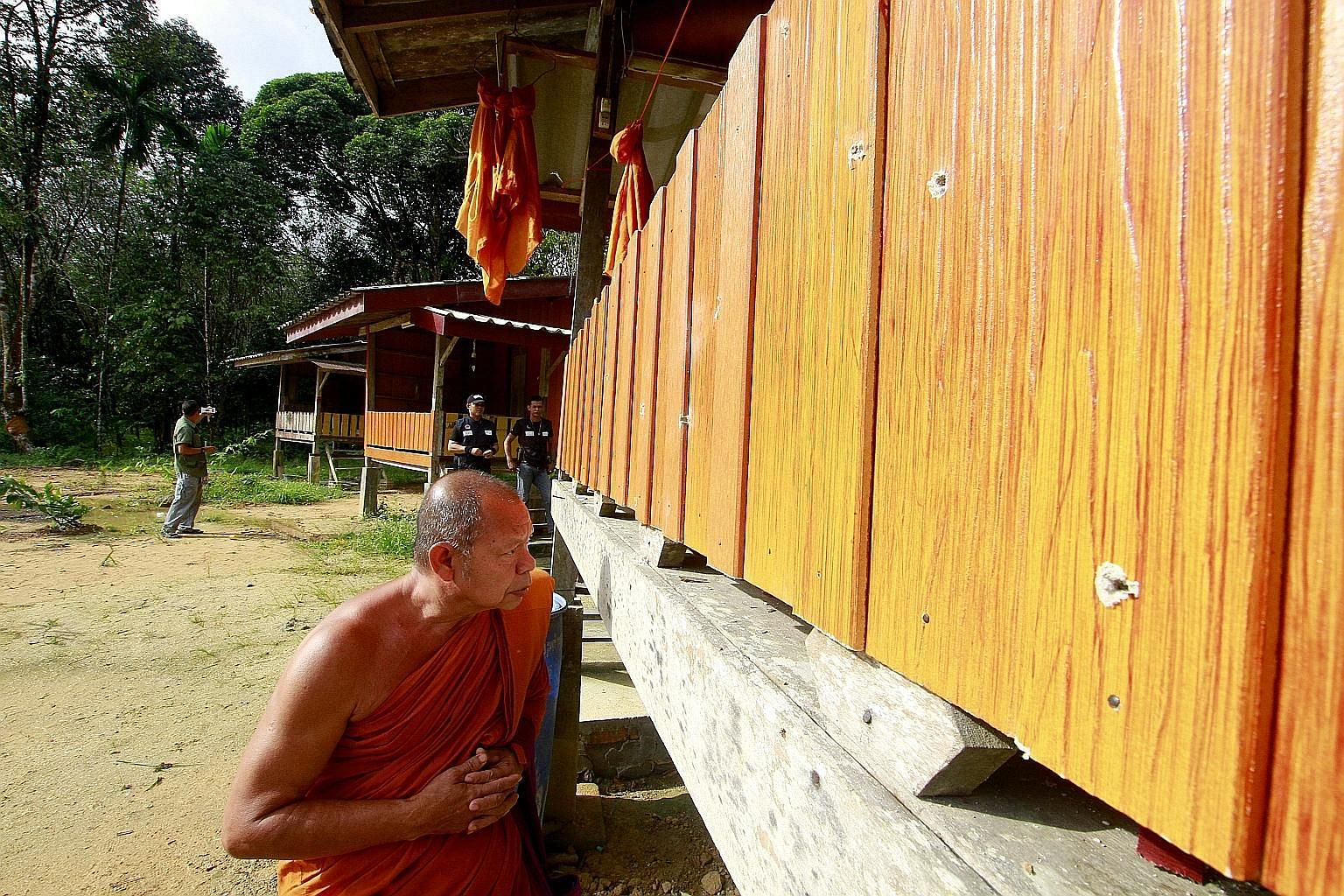 A Buddhist monk looking at bullet holes in the wall of a monk's shelter at the Rattanupap temple in Narathiwat province yesterday.