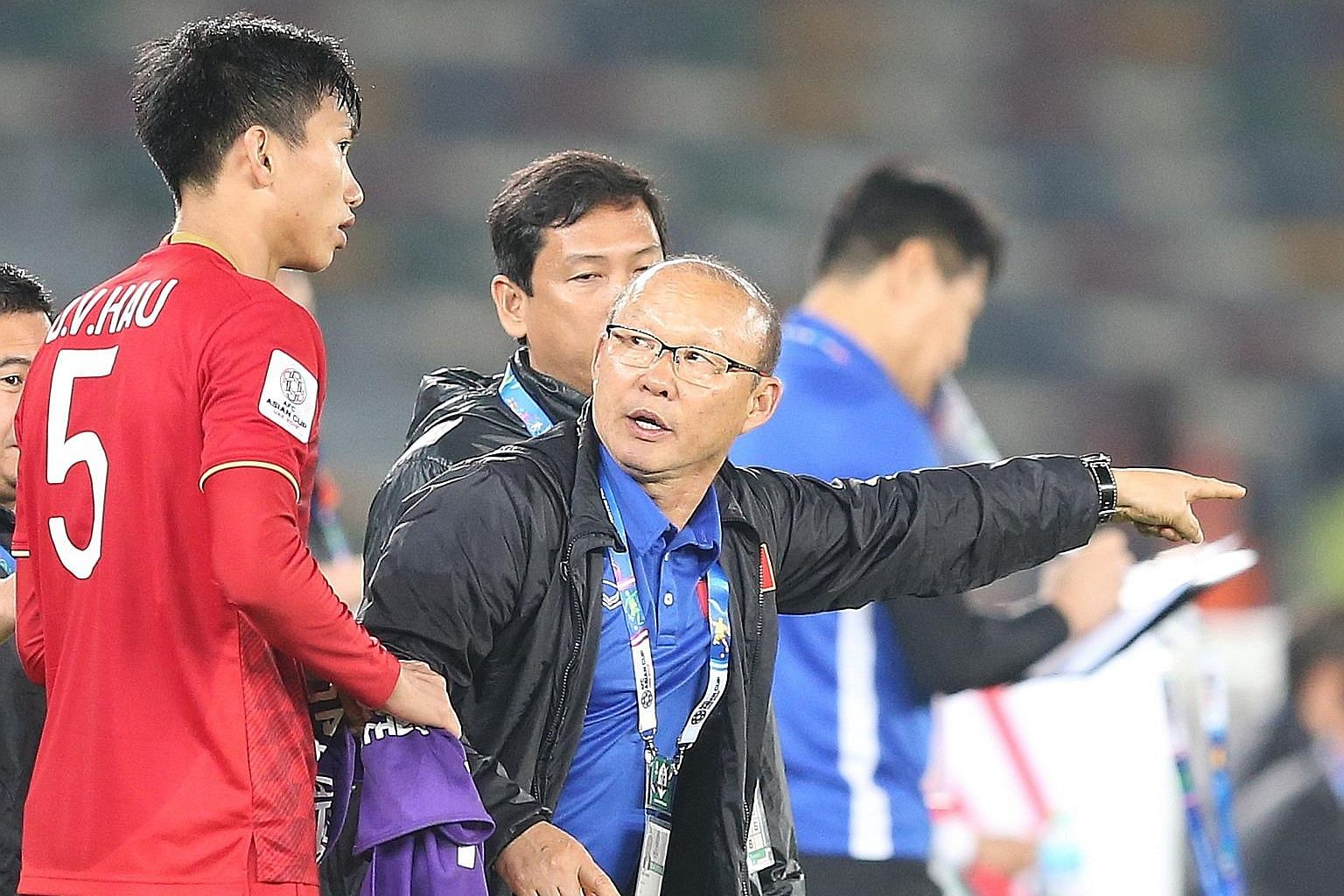 Vietnamese football fans cheering their national team in an AFF Suzuki Cup semi-final match, with one of them seen here sporting an image of head coach Park Hang-seo on his body as he celebrates victory with others.