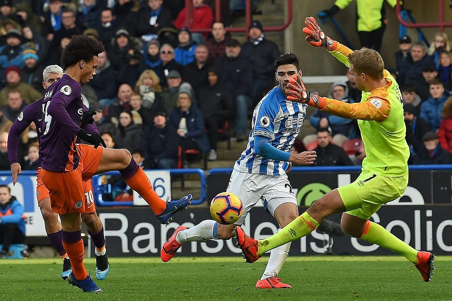 Manchester City's German midfielder Leroy Sane shoots past Huddersfield goalkeeper Jonas Lossl to score their third goal in the 3-0 victory yesterday.