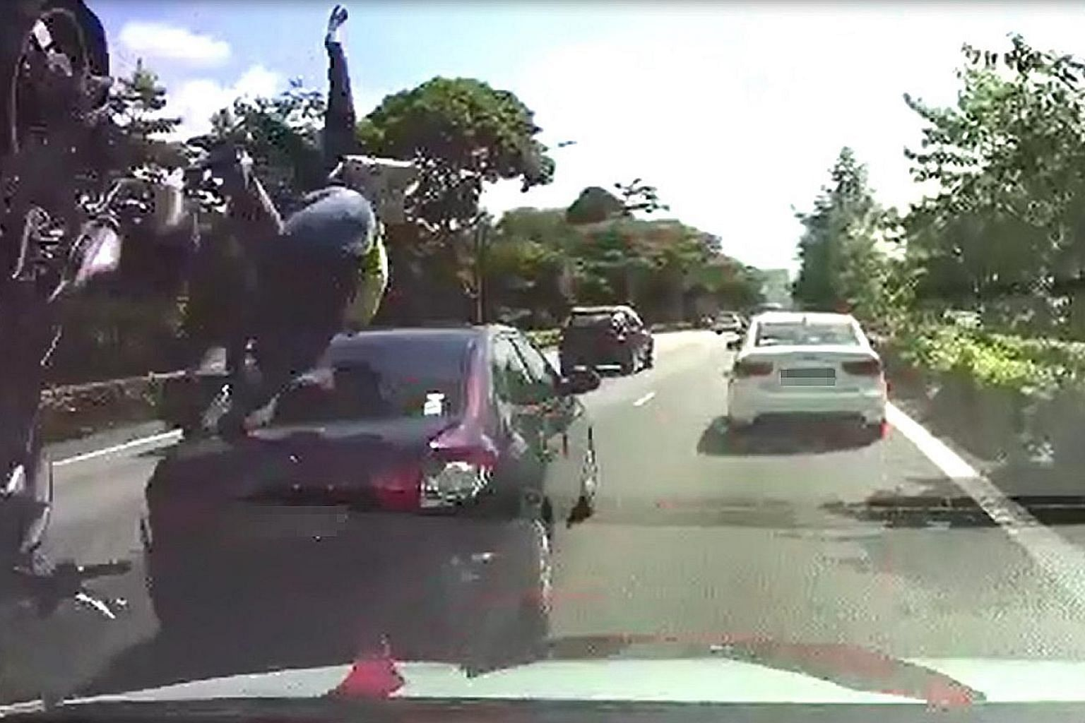 A dashcam video sent to Lianhe Wanbao showed the motorcyclist landing on the car after he collided with it. His pillion rider was flung in front of the car.