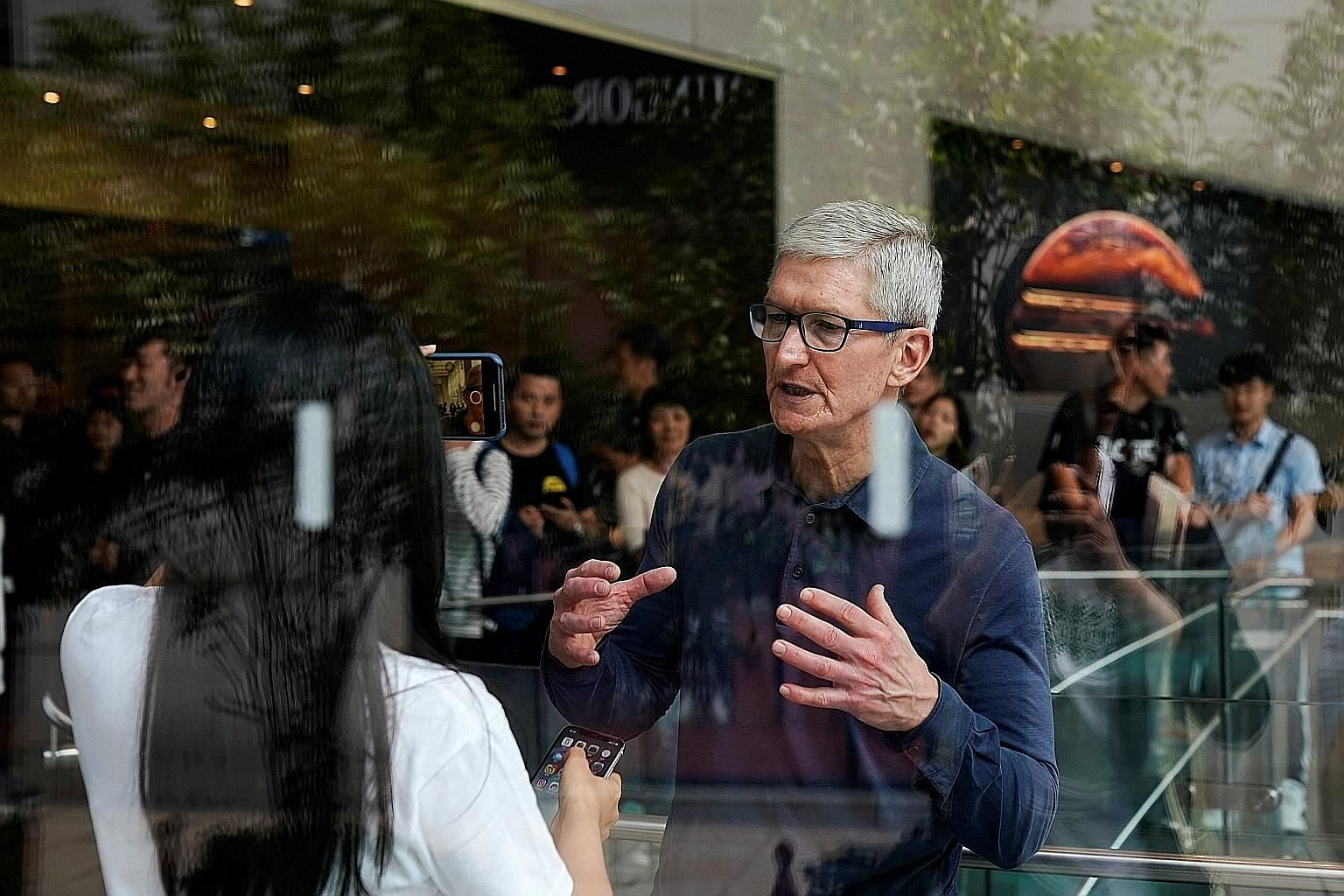 Apple CEO Tim Cook visiting an Apple store in Shanghai last October. Mr Cook was among those who called for a retraction after the Bloomberg Businessweek report on an alleged breach of US computer infrastructure by China. Former Trump lawyer Michael