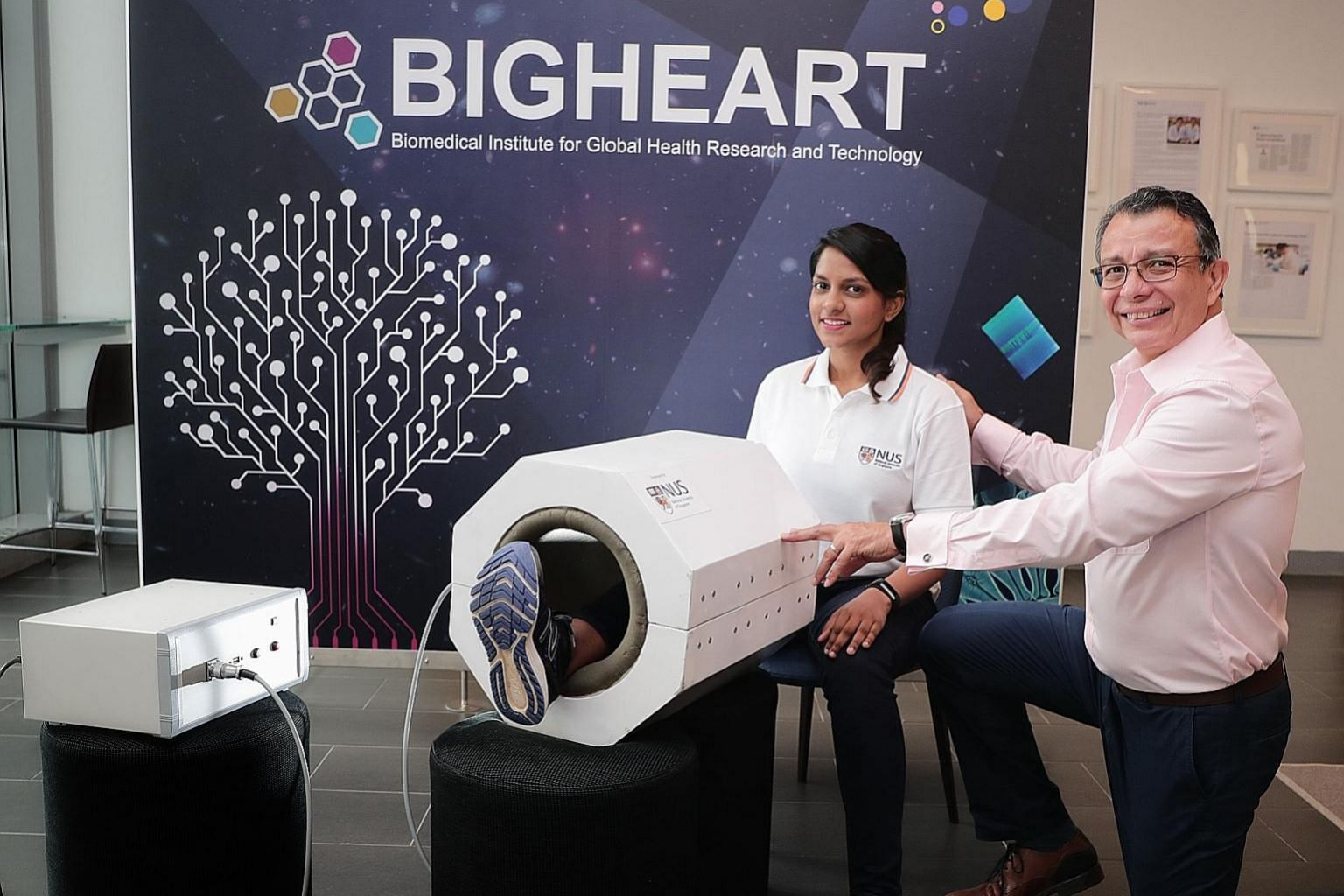 Research assistant Sharanya Ramanan showing how MRegen works, with Associate Professor Alfredo Franco-Obregon. The machine's prototype resembles a miniature MRI scanner that is large enough for a person to insert one leg.