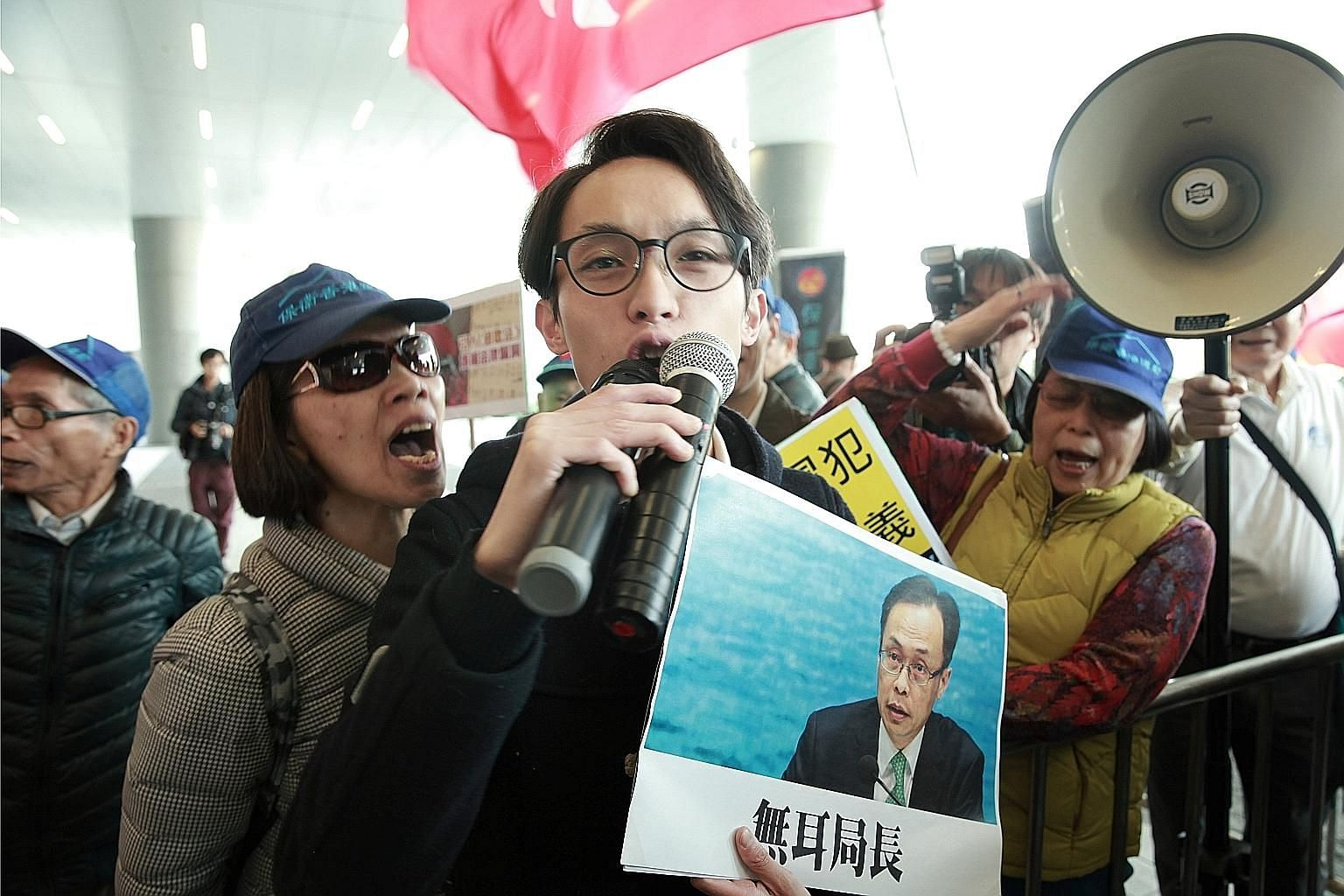 A pro-democracy activist holding a sign showing Secretary for Constitutional and Mainland Affairs Patrick Nip in Hong Kong yesterday.