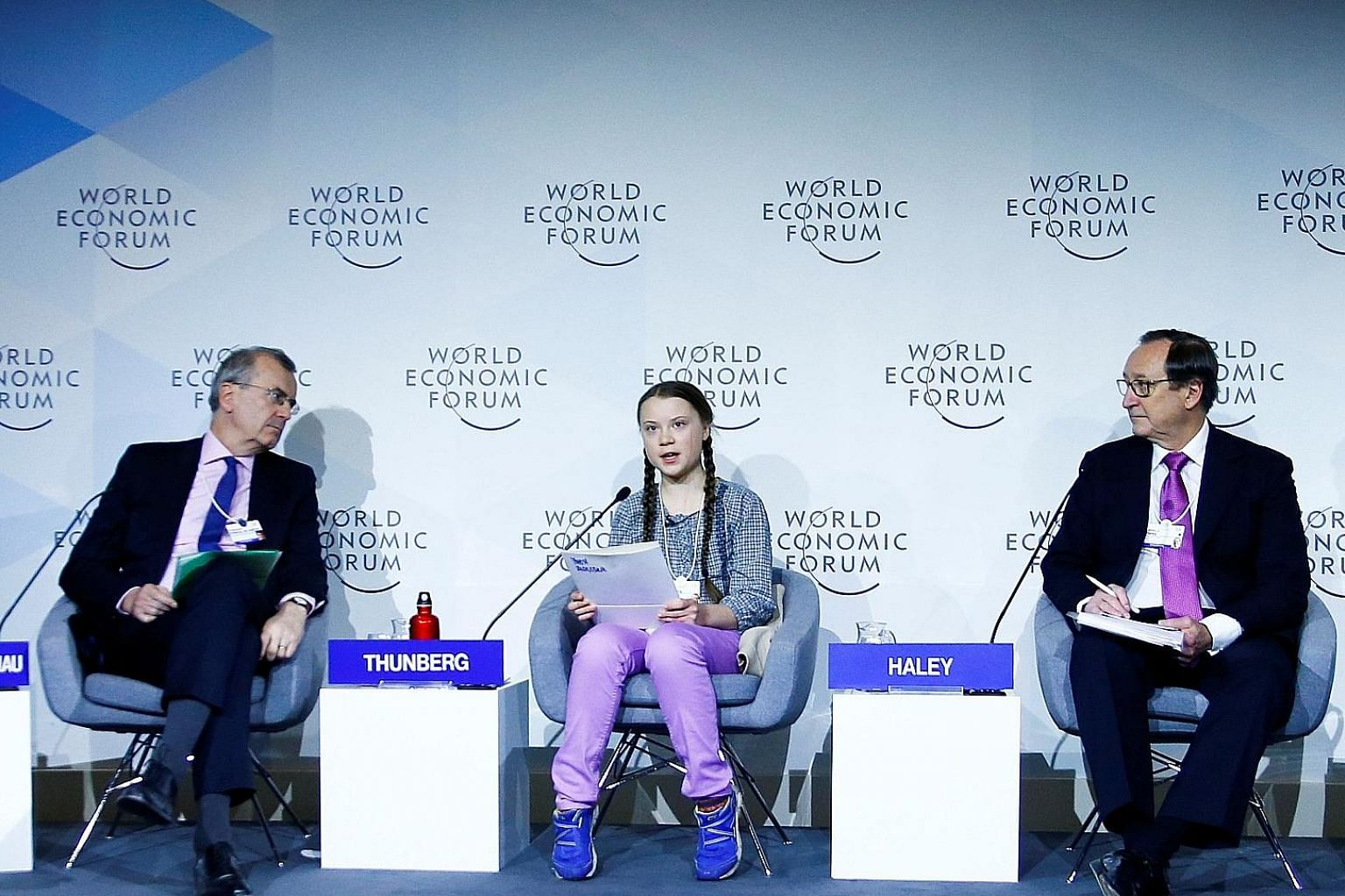 Young climate crusader Greta Thunberg with French central bank governor Francois Villeroy de Galhau (left) and consultancy firm Willis Towers Watson's CEO John Haley at a WEF panel discussion in Davos yesterday.