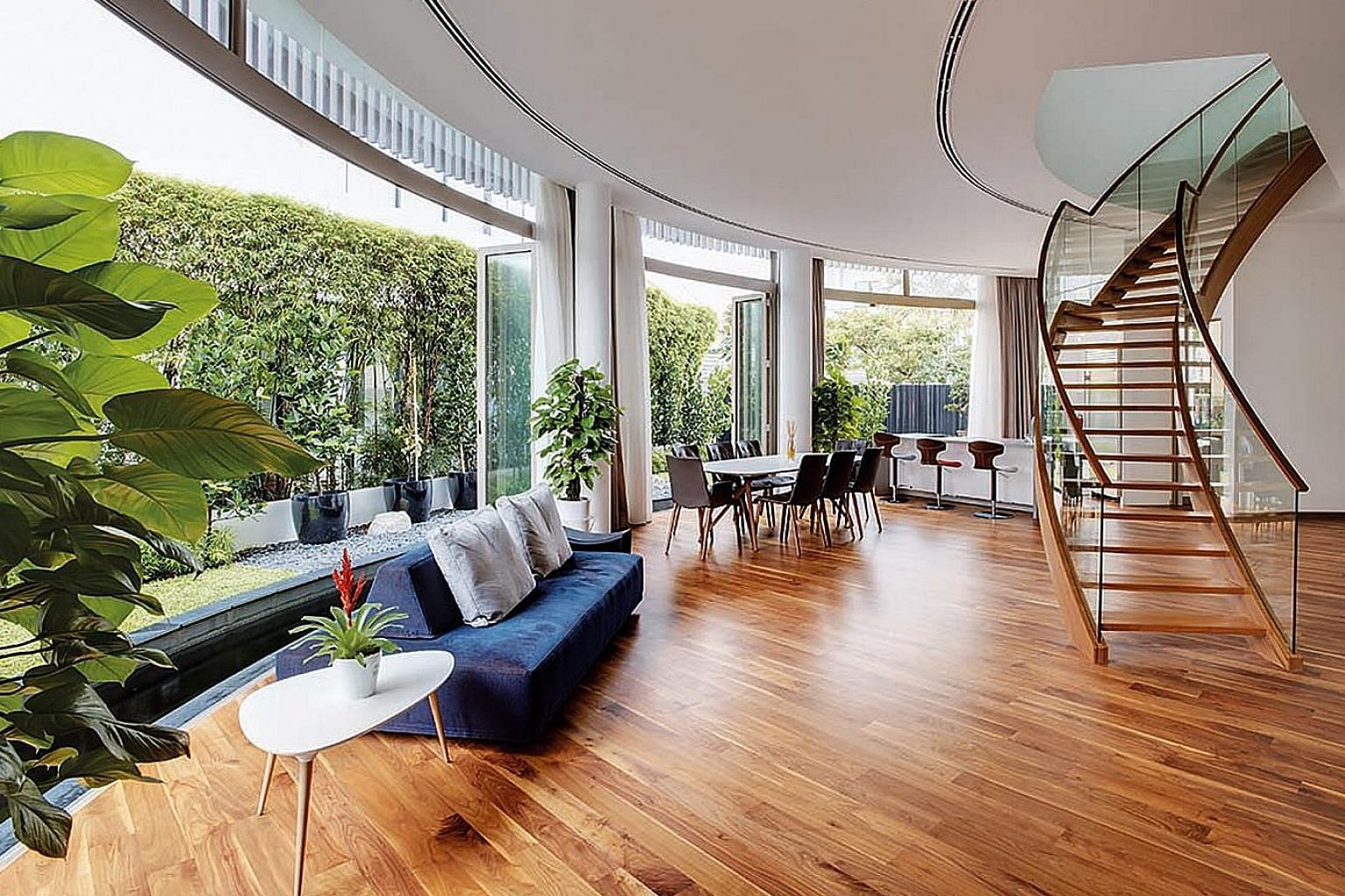 """Deep eaves shelter the entertainment room housed in the glass attic. The elegance, lightness and porosity of the curved staircase, constructed of mild steel and with timber veneer cladding, complement the """"floating"""" quality of the house. The facade t"""