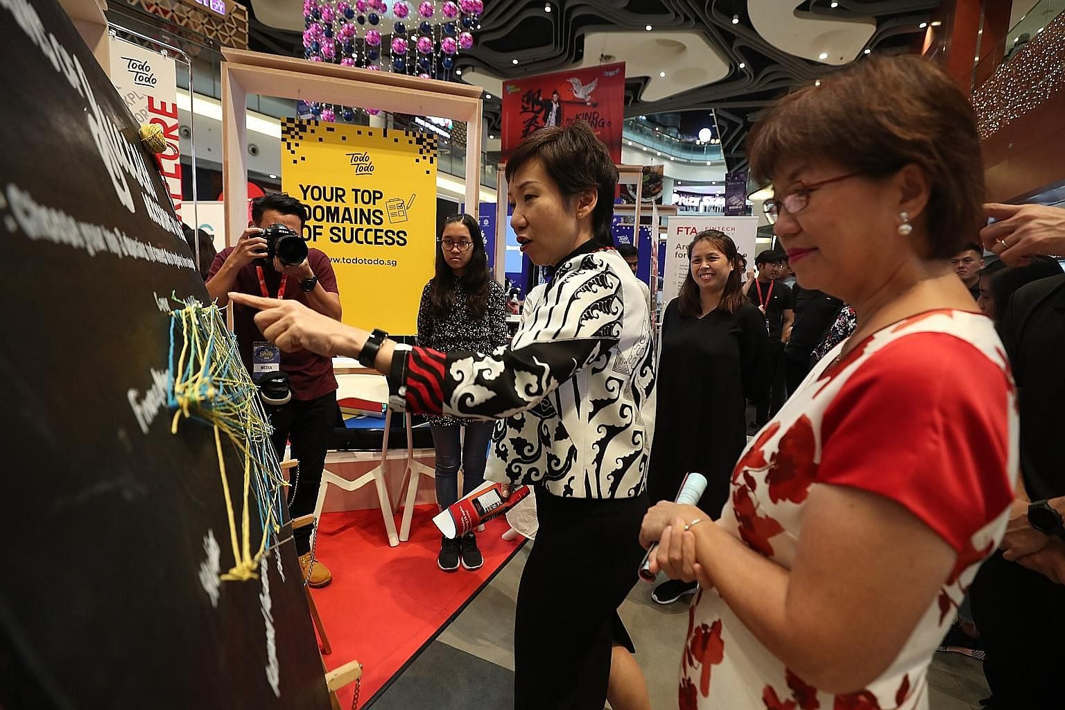 Minister for Culture, Community and Youth Grace Fu (left) and Ms Denise Phua, Mayor of Central Singapore District, at one of the booths at the Todo Todo Skills Marketplace fair yesterday. Todo Todo is a career support initiative started by NTUC and t