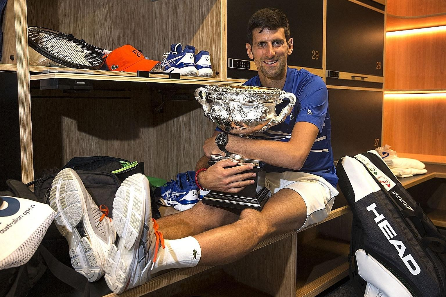 World No. 1 Novak Djokovic posing with the Norman Brookes Challenge Cup in the men's locker room after defeating Rafael Nadal in the men's singles final at the Australian Open in Melbourne yesterday.