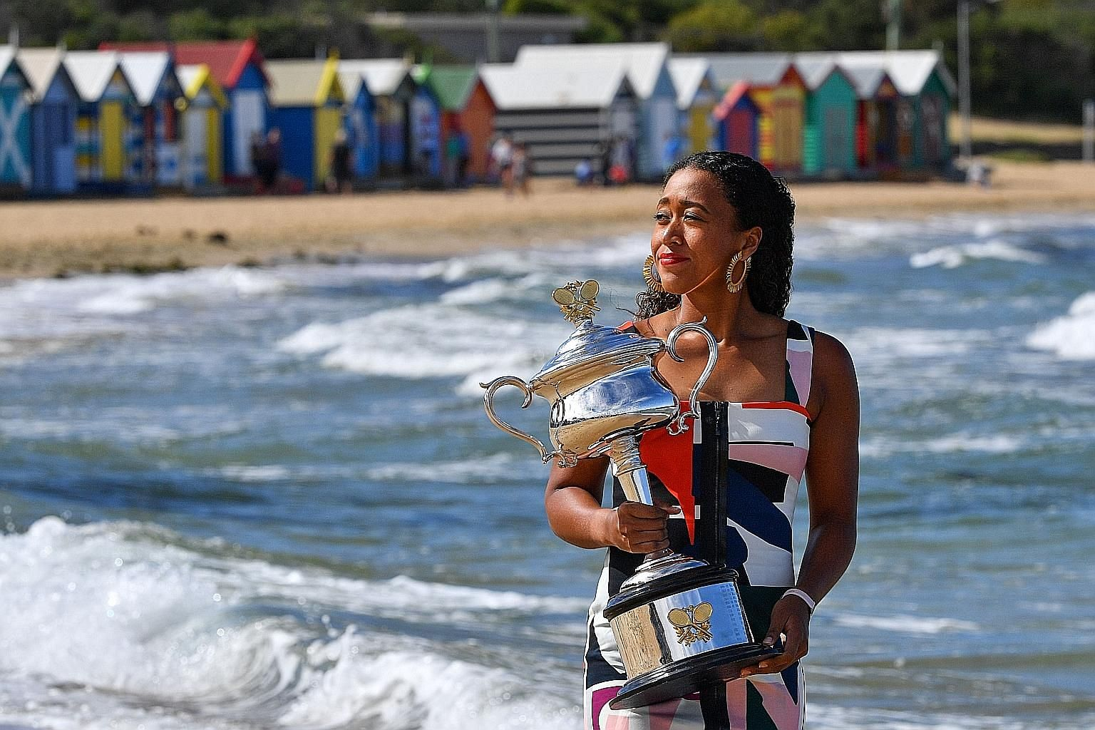 Australian Open winner Naomi Osaka holding the championship trophy at Brighton Beach in Melbourne yesterday. The 21-year-old Japanese will rise to world No. 1 today.