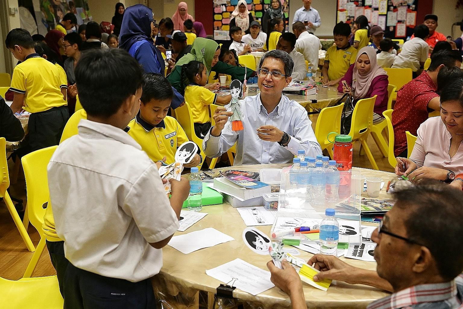 Senior Parliamentary Secretary for Education Muhammad Faishal Ibrahim joining pupils and parents in a Storygami activity during a workshop on reading using the Nabil Nabilah Reader Series, at Punggol View Primary School yesterday.