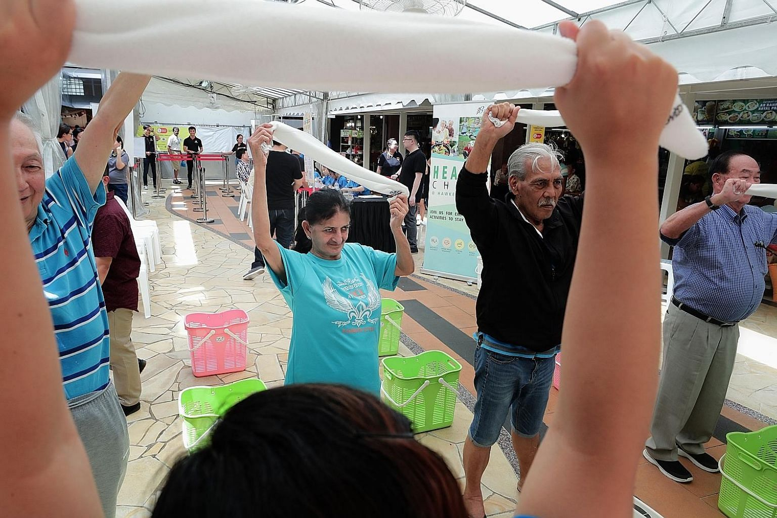 The public trying out the towel exercise at the launch of the Health Promotion Board's Health Chats @ Hawker Centres on Wednesday. The programme targets mature hawker centre workers, who tend to have limited access to health checks and health and saf