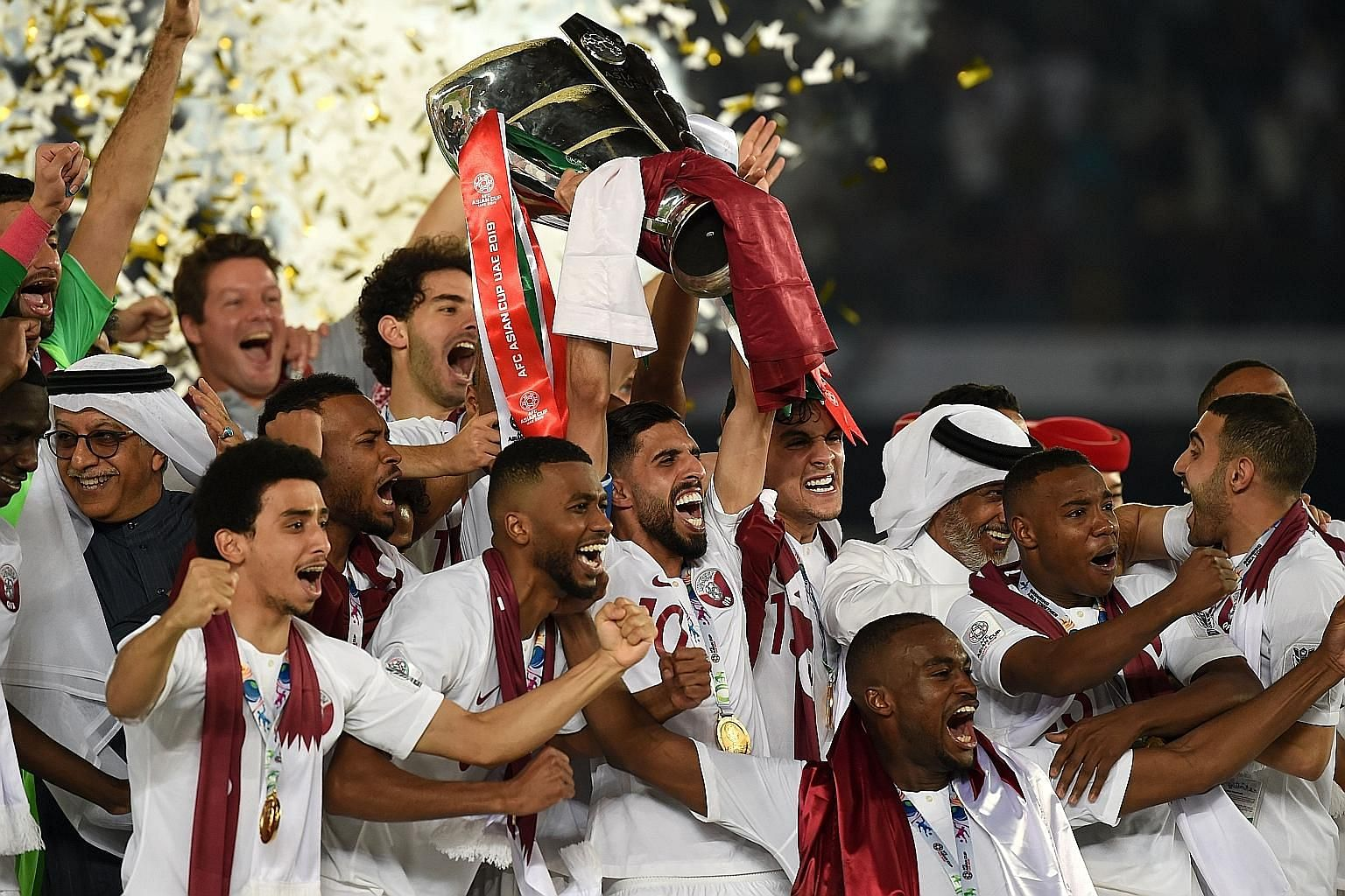 Qatar's players with the trophy after beating Japan 3-1 in the Asian Cup final at the Mohammed Bin Zayed Stadium in Abu Dhabi on Friday. Their head coach Felix Sanchez led Qatar to their first Asian Under-19 title in 2014. They also reached the U-23