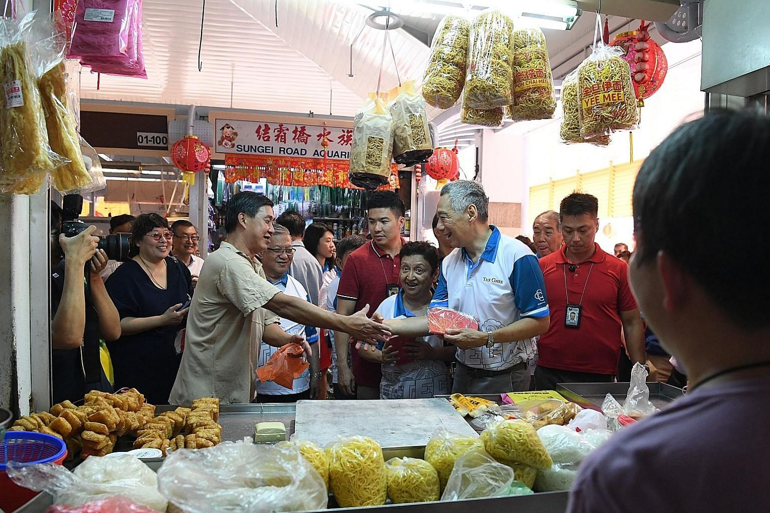 Prime Minister Lee Hsien Loong greeting a stall owner during a visit yesterday to Teck Ghee market in Ang Mo Kio, where he met residents and stall owners to exchange New Year greetings and give out red packets.