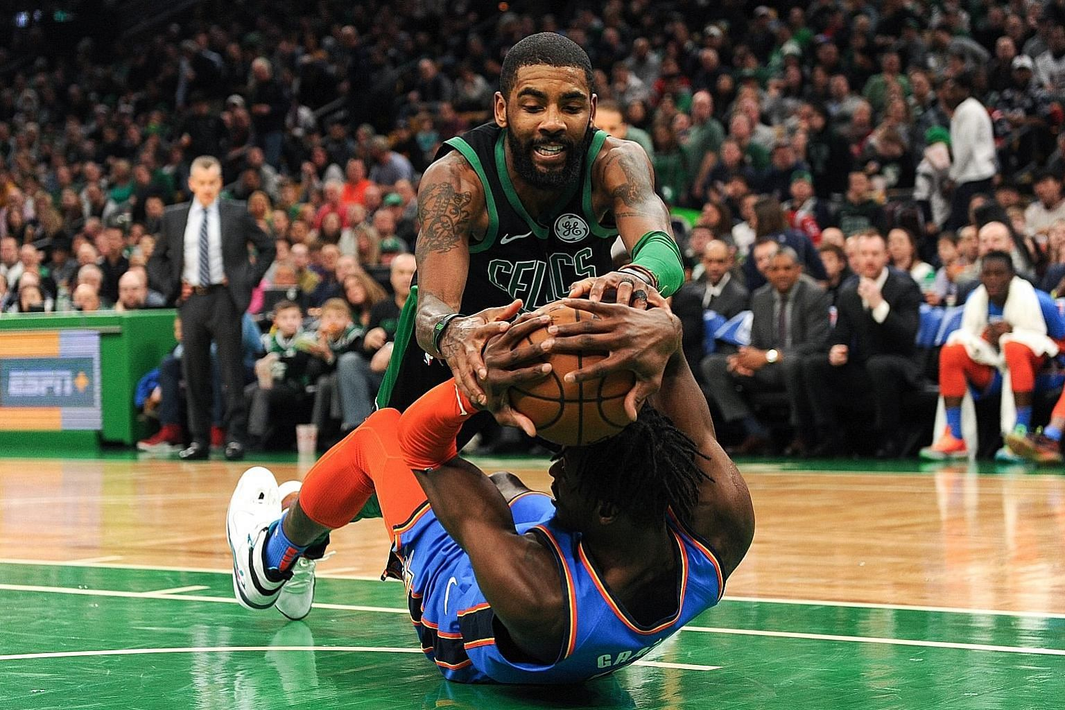Boston Celtics guard Kyrie Irving and Oklahoma City Thunder forward Jerami Grant tussling for the ball during the second half of their NBA game at TD Garden on Sunday. Irving hit 30 points and had 11 assists in his team's 134-129 win.