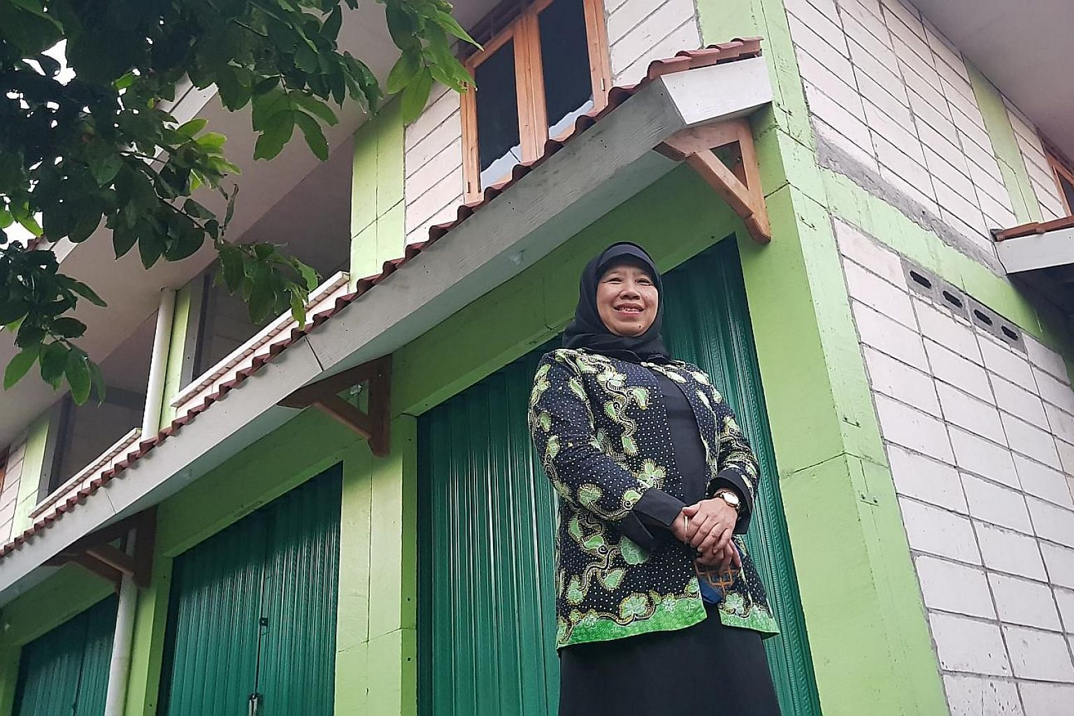 Shopkeeper Ngadiyem in front of her dome house - one of 80 such houses in New Ngelepen village in Sleman. They are made of concrete and reinforced with steel, which can help them withstand storms and quakes. They also look similar to the homes in the