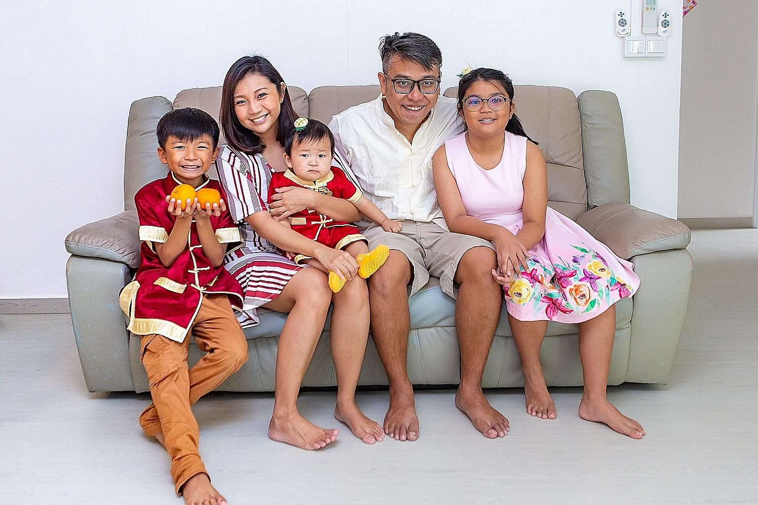 Ms Lim Zihui with her husband Royston Yap, 37, and their children - Nathan, eight; Nigel, eight months old; and Noelyn, 11 - in their Punggol executive apartment, which is near her parents' home.