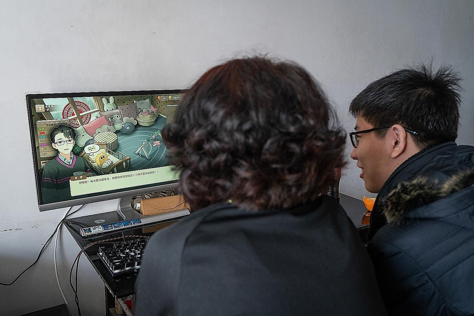 Mr Kang Shenghao, 19, playing the video game Chinese Parents with his mother.